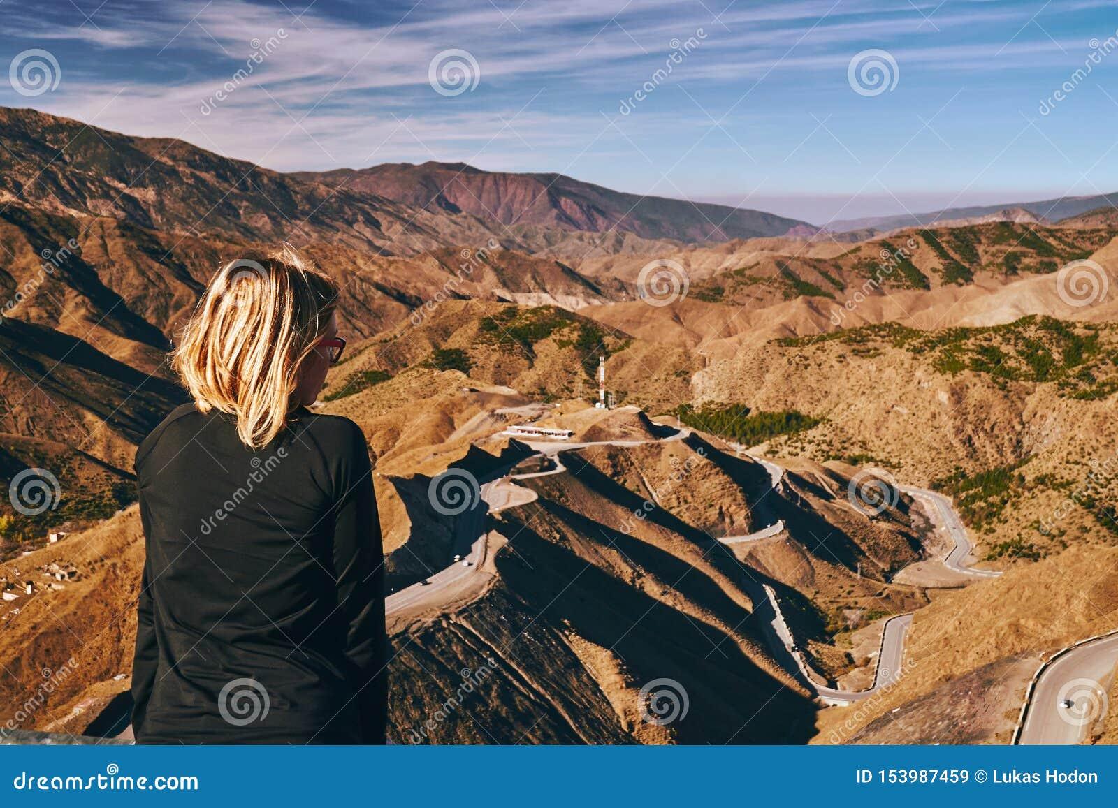 La jeune fille blonde médite au-dessus du panorama du passage de montagne de Tizi n Tichka au Maroc