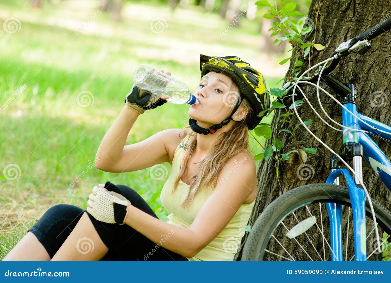 La jeune fille boit l eau d une bouteille après faire du vélo de montagne