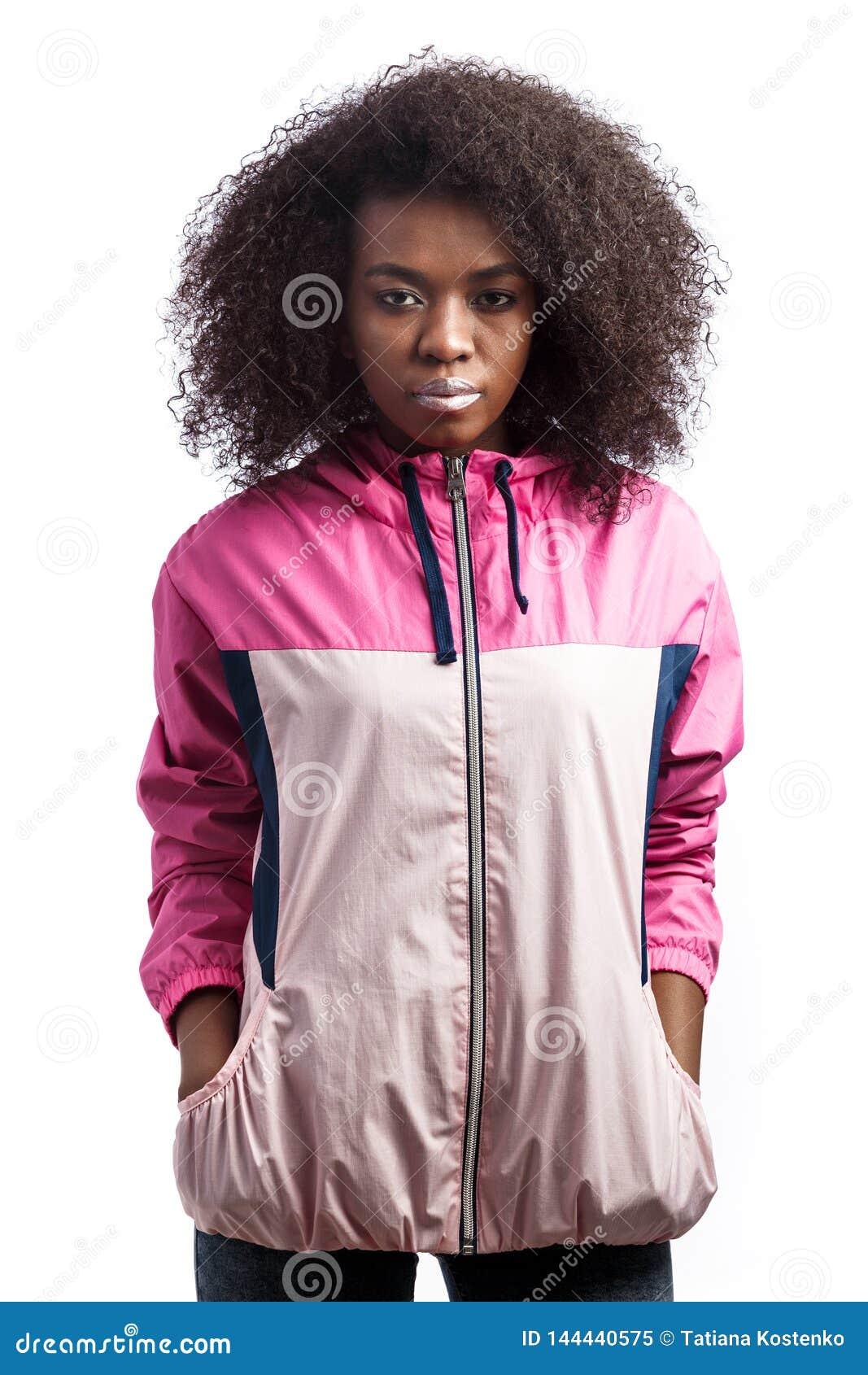 La jeune fille châtain bouclée habillée dans la veste de sport rose se tient au fond blanc dans le studio