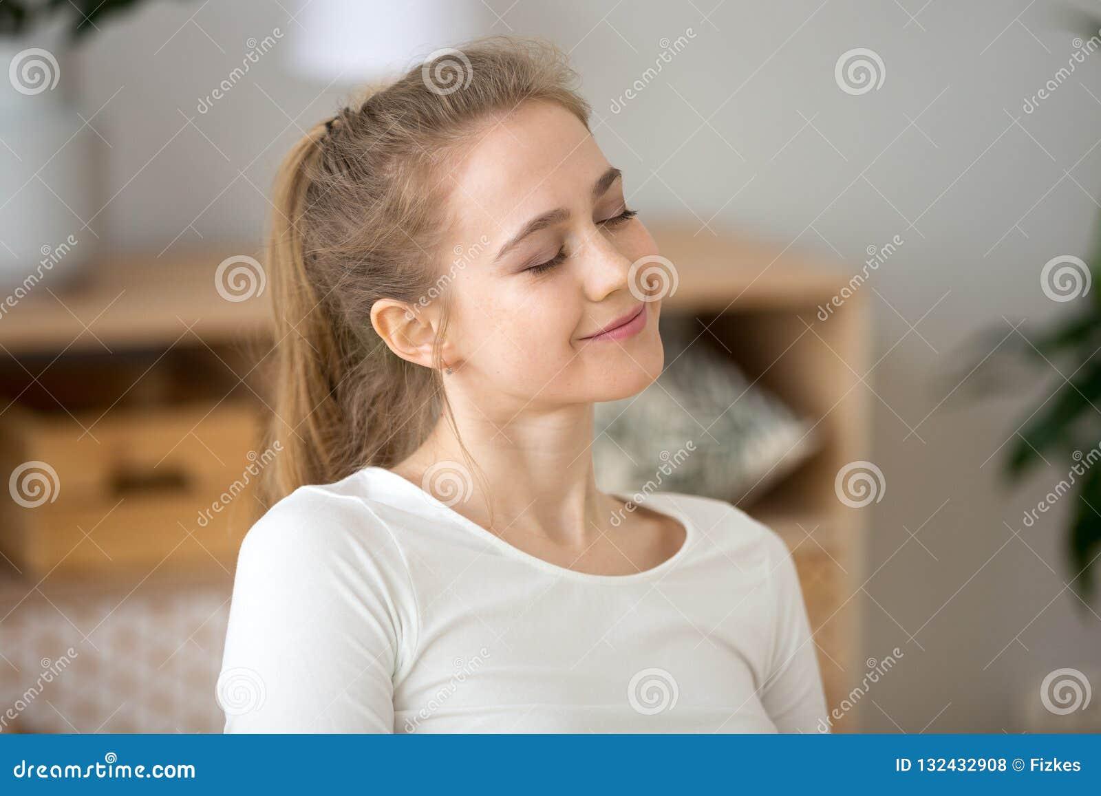 La jeune fille heureuse avec des yeux a clôturé rêver à la maison