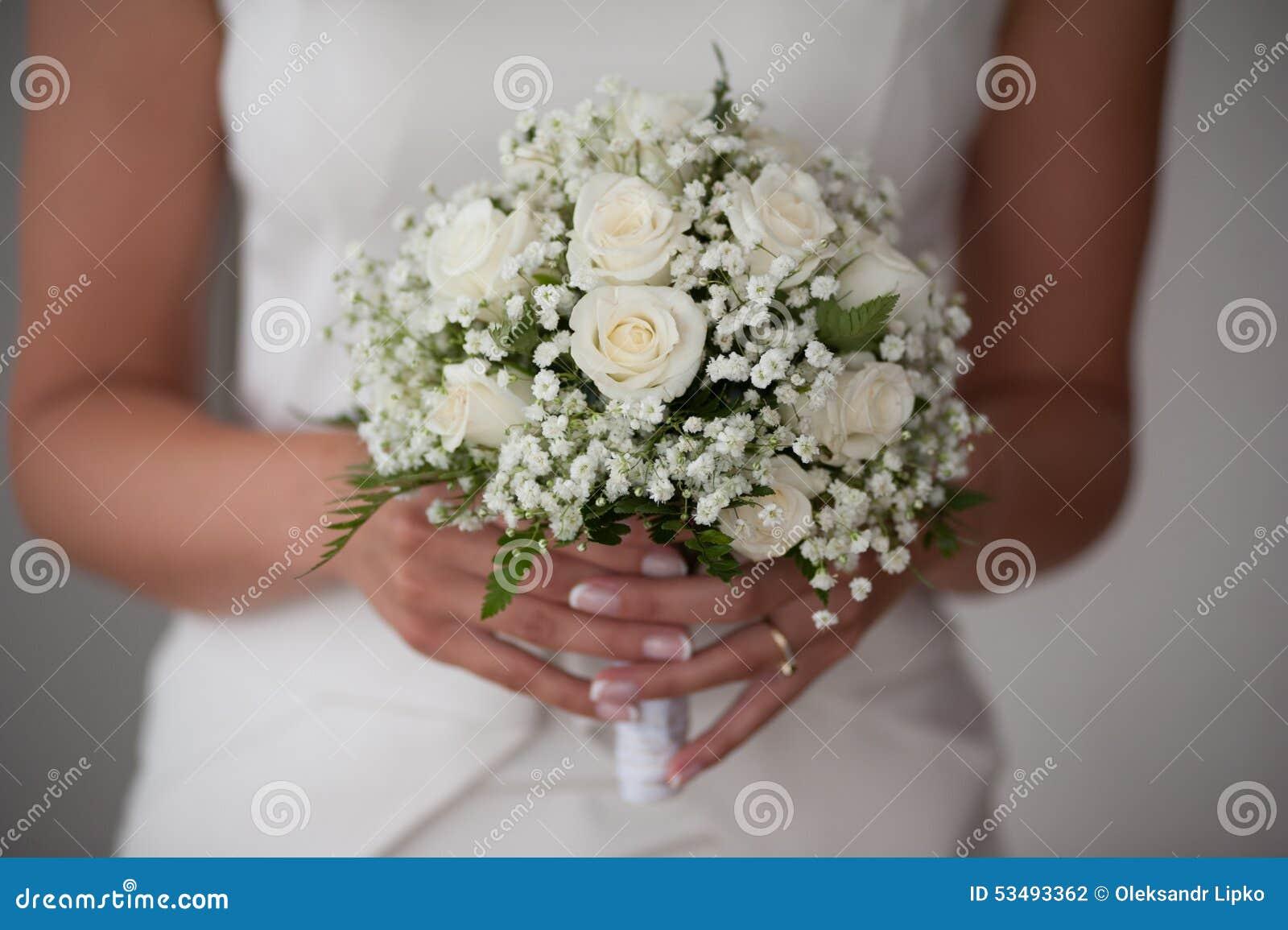 la jeune fille-jeune mariée ou demoiselle d'honneur tient un bouquet