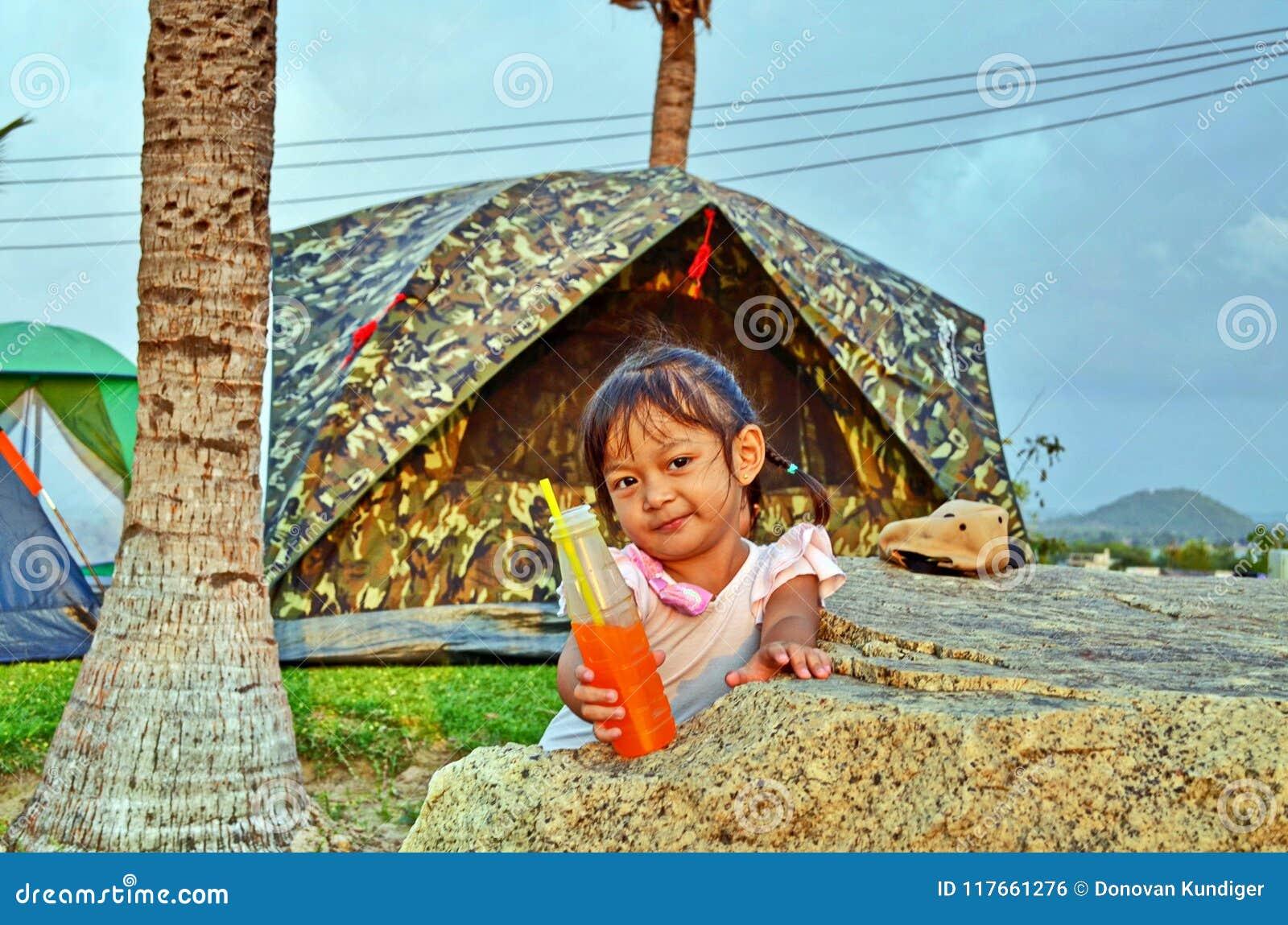 La jeune fille offre son orangeade dans un terrain de camping