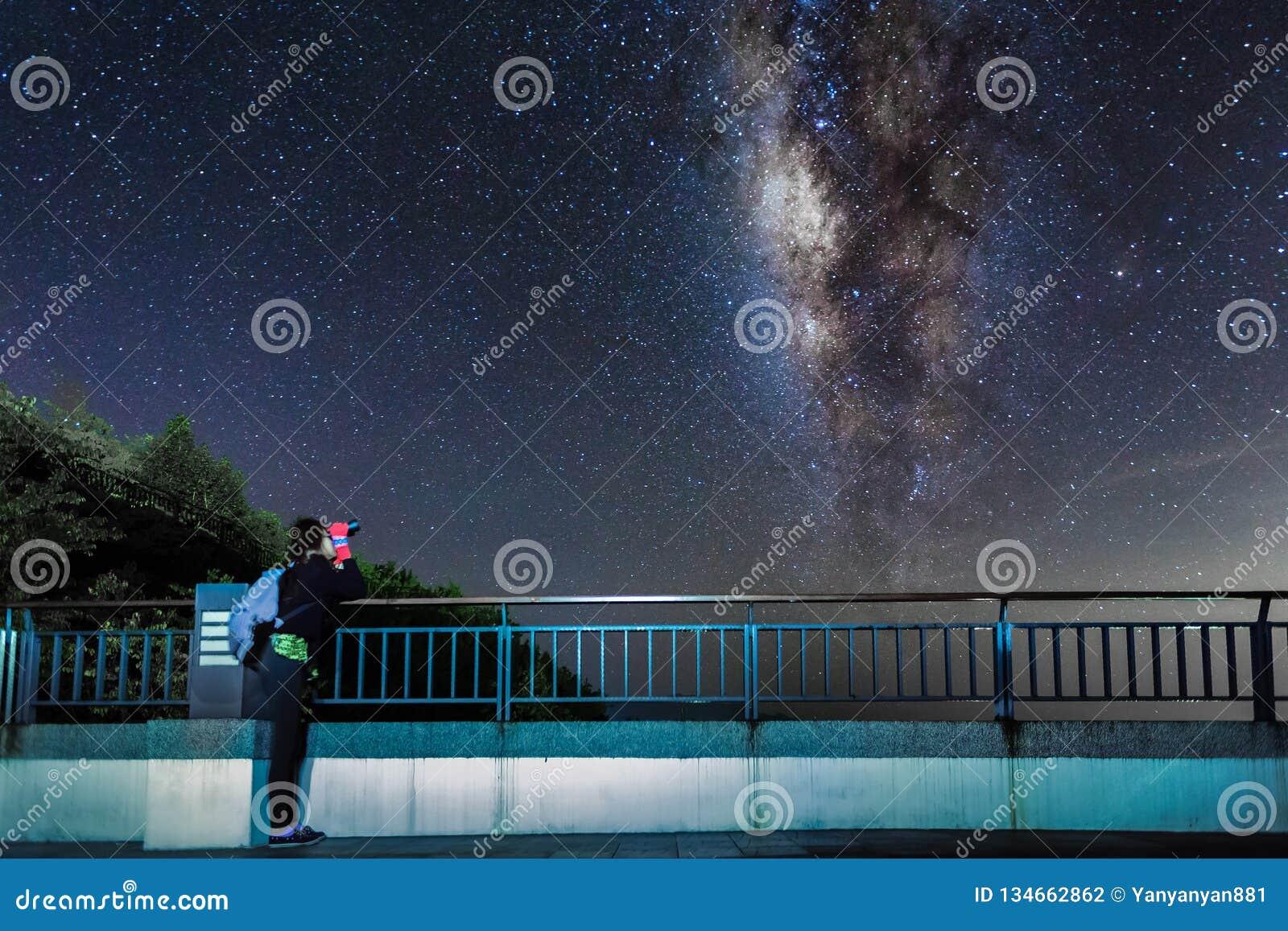 La jeune fille regarde le ciel nocturne et la galaxie de manière laiteuse avec binoculaire