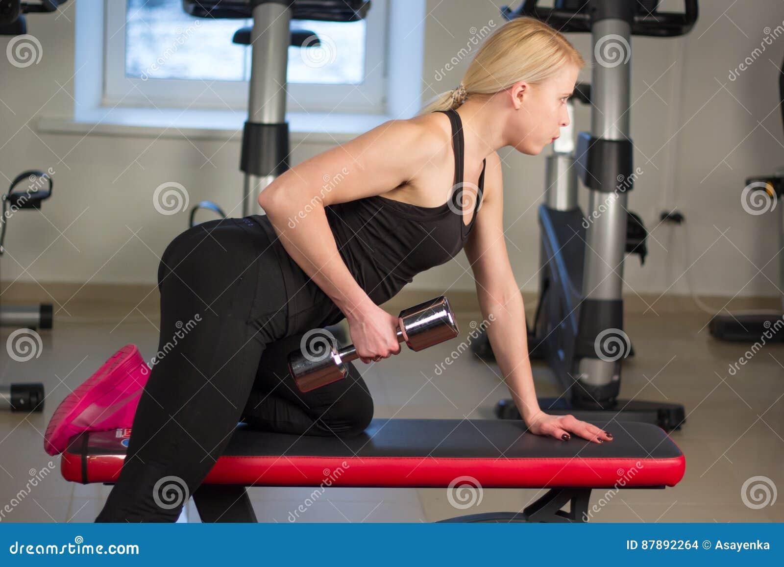 La jeune fille sexy d athlétisme faisant des haltères pressent des exercices La forme physique muscled la femme dans la séance d