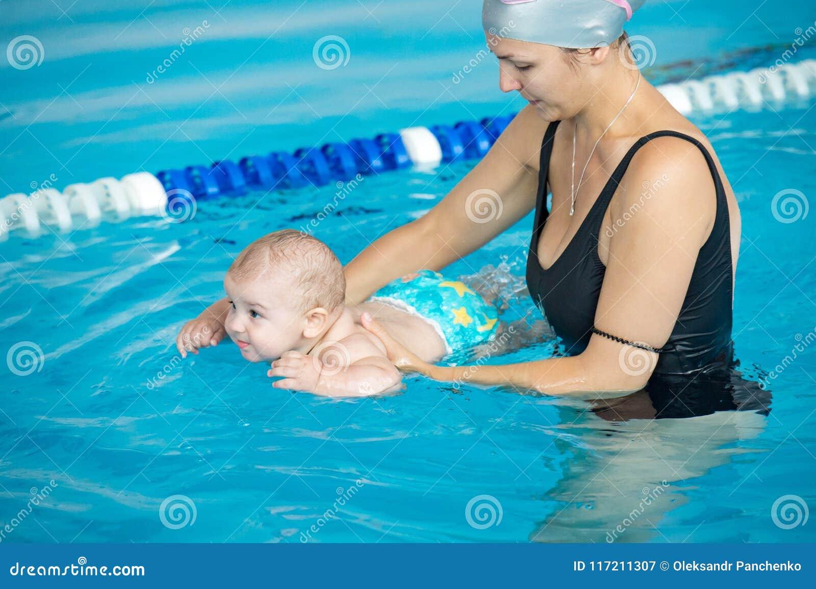 La jeune mère enseignent son petit fils, comment nager dans un poo de natation