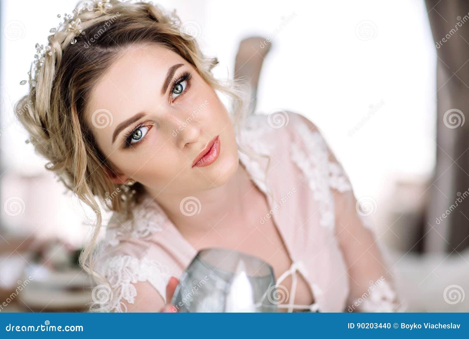 La jeune mariée dans un peignoir à la fenêtre de chambre à coucher pendant le matin