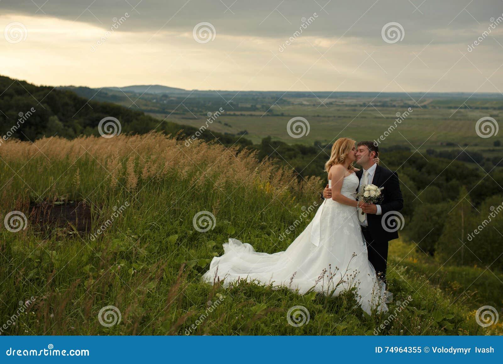 La jeune mariée embrasse le visage du marié tendrement tandis qu ils se tiennent sur un h vert