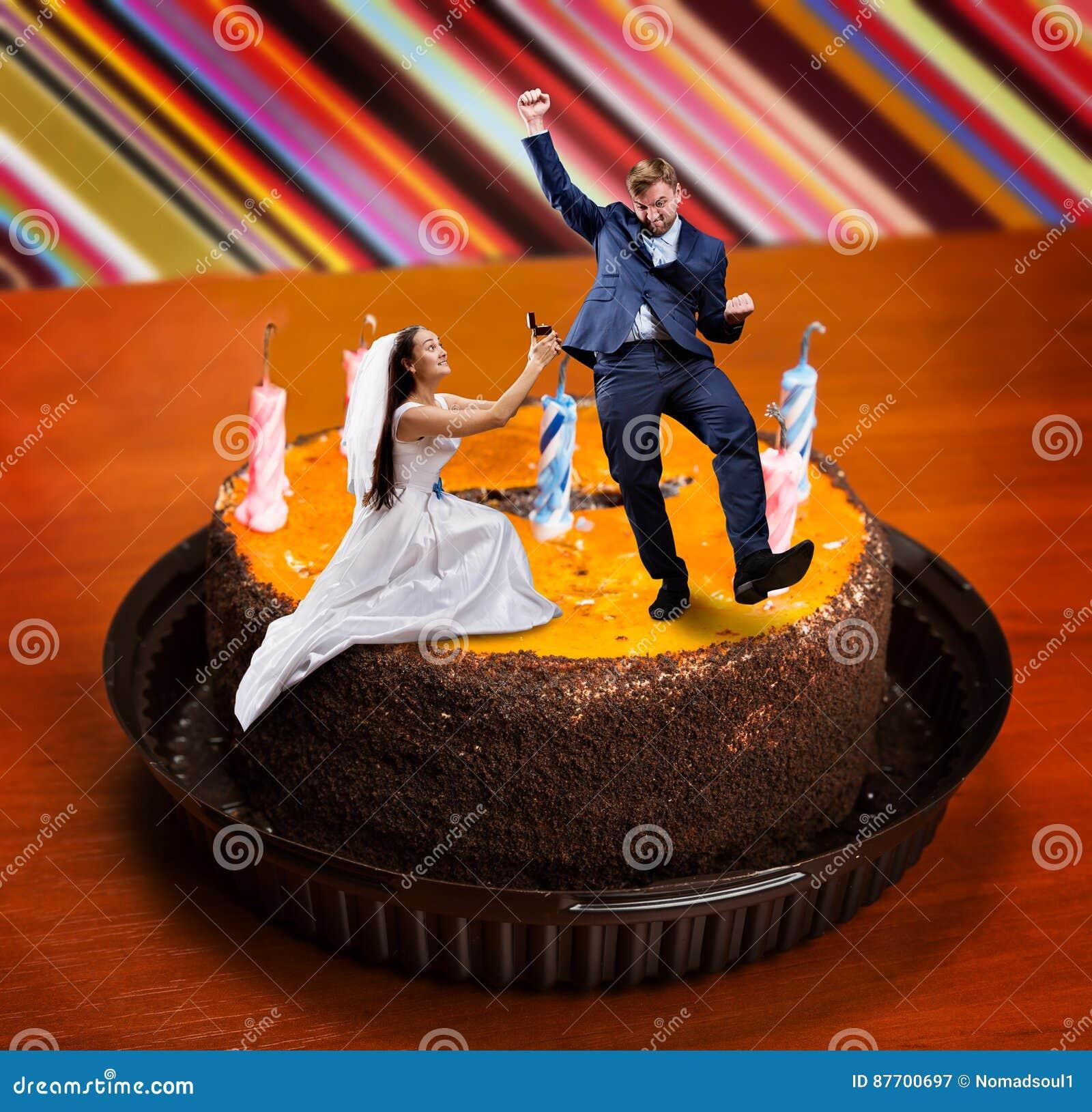 La jeune mariée fait la proposition au marié sur le grand gâteau