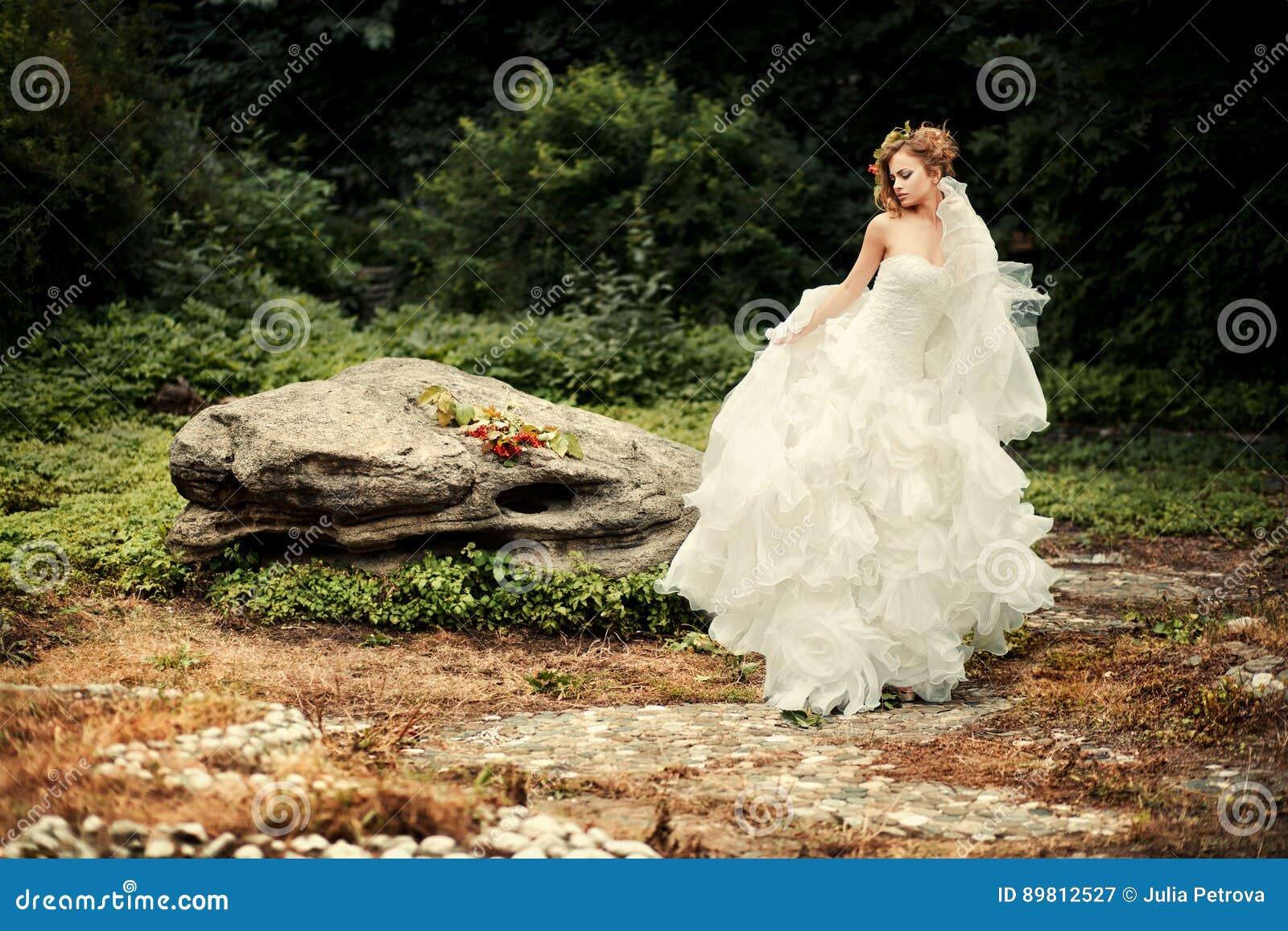 La jeune mariée magnifique dans une robe blanche luxuriante danse