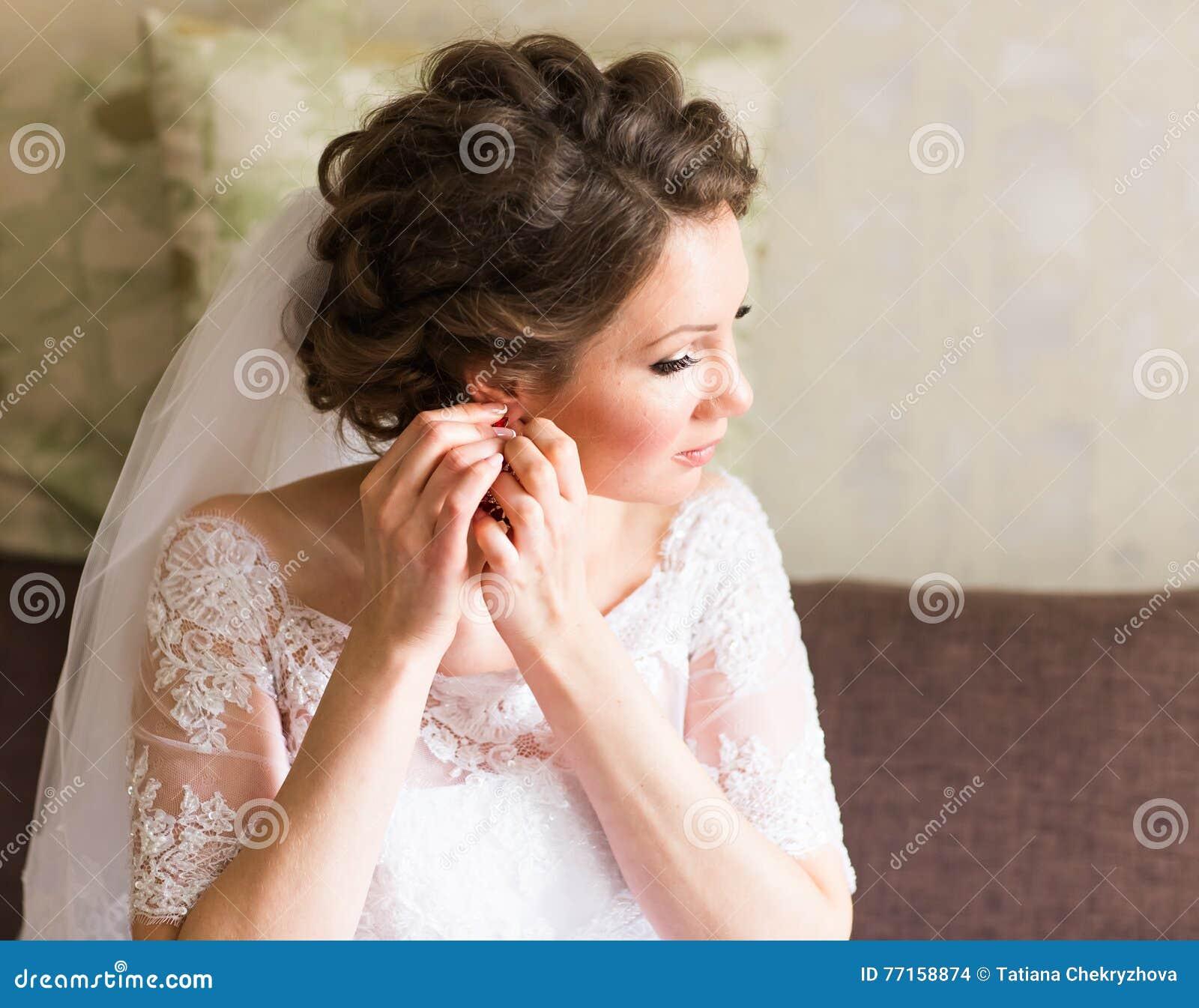 La jeune mariée prend les boucles d oreille, épousant la préparation