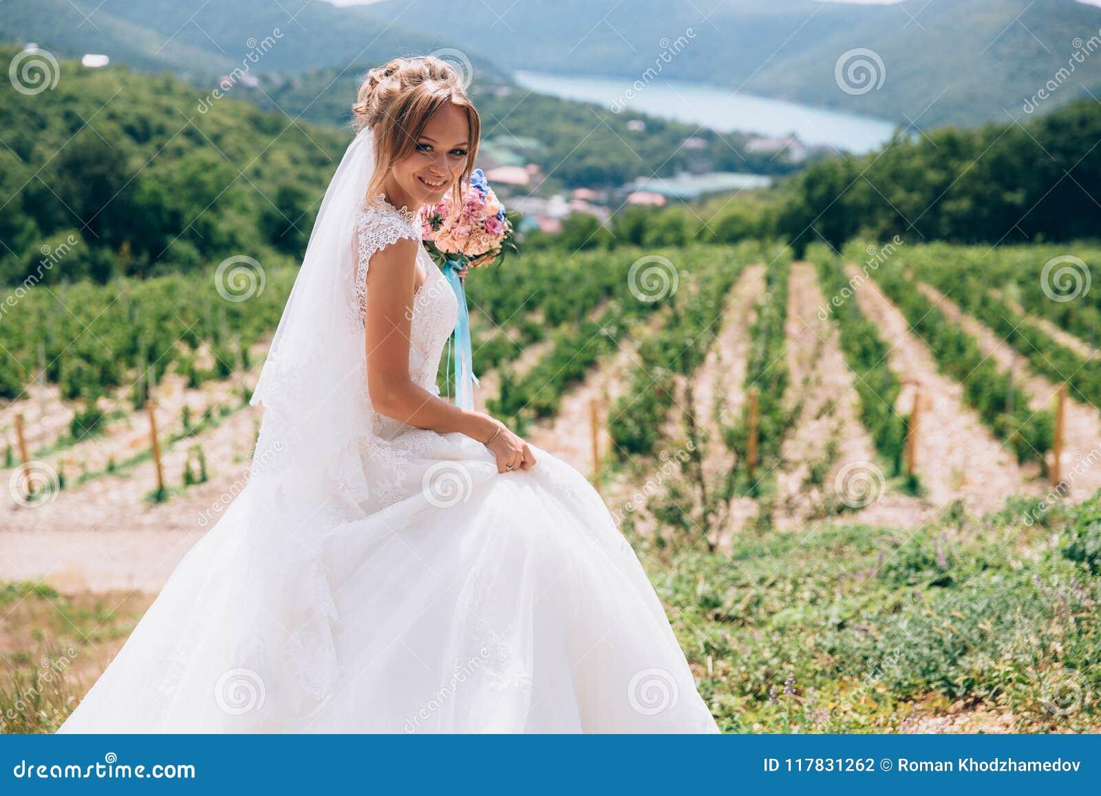 La jeune mariée rit et se réjouit pendant le jour ensoleillé La fille tient un bouquet chic des fleurs dans ses mains et promenad
