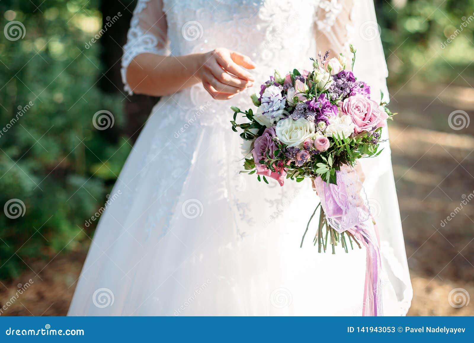 La jeune mariée tient un bouquet l épousant, robe de mariage