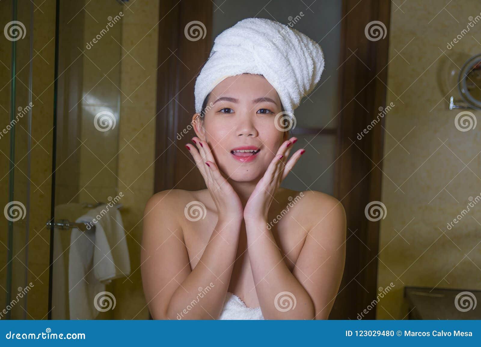 La jeune salle de bains coréenne asiatique heureuse et belle de femme à la maison avec le chef de serviette a enveloppé le visage