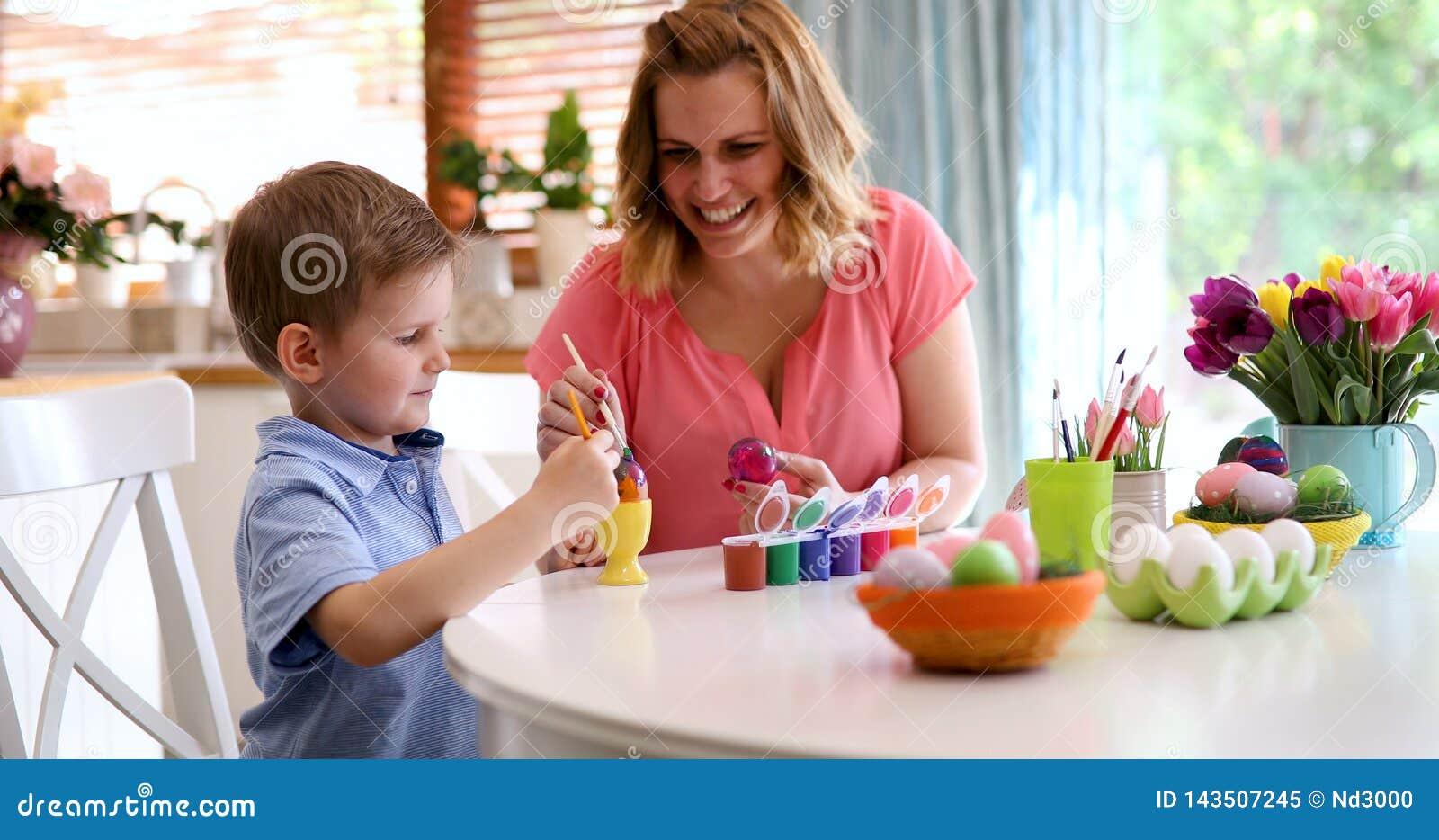 La jeunes mère et fils heureux peignent des oeufs de pâques