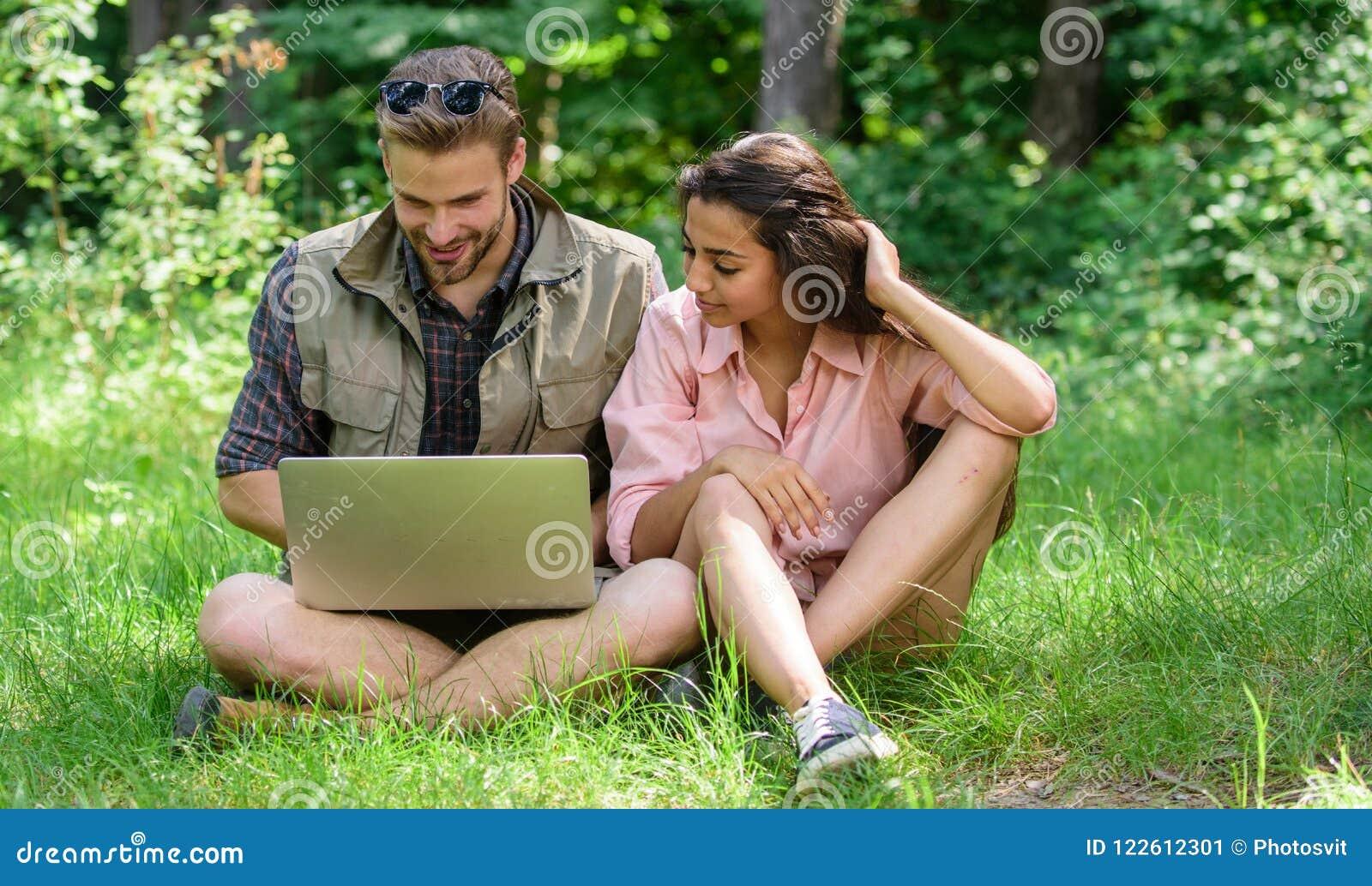 La jeunesse de couples dépensent des loisirs dehors avec l ordinateur portable Les technologies modernes en donnent l occasion d