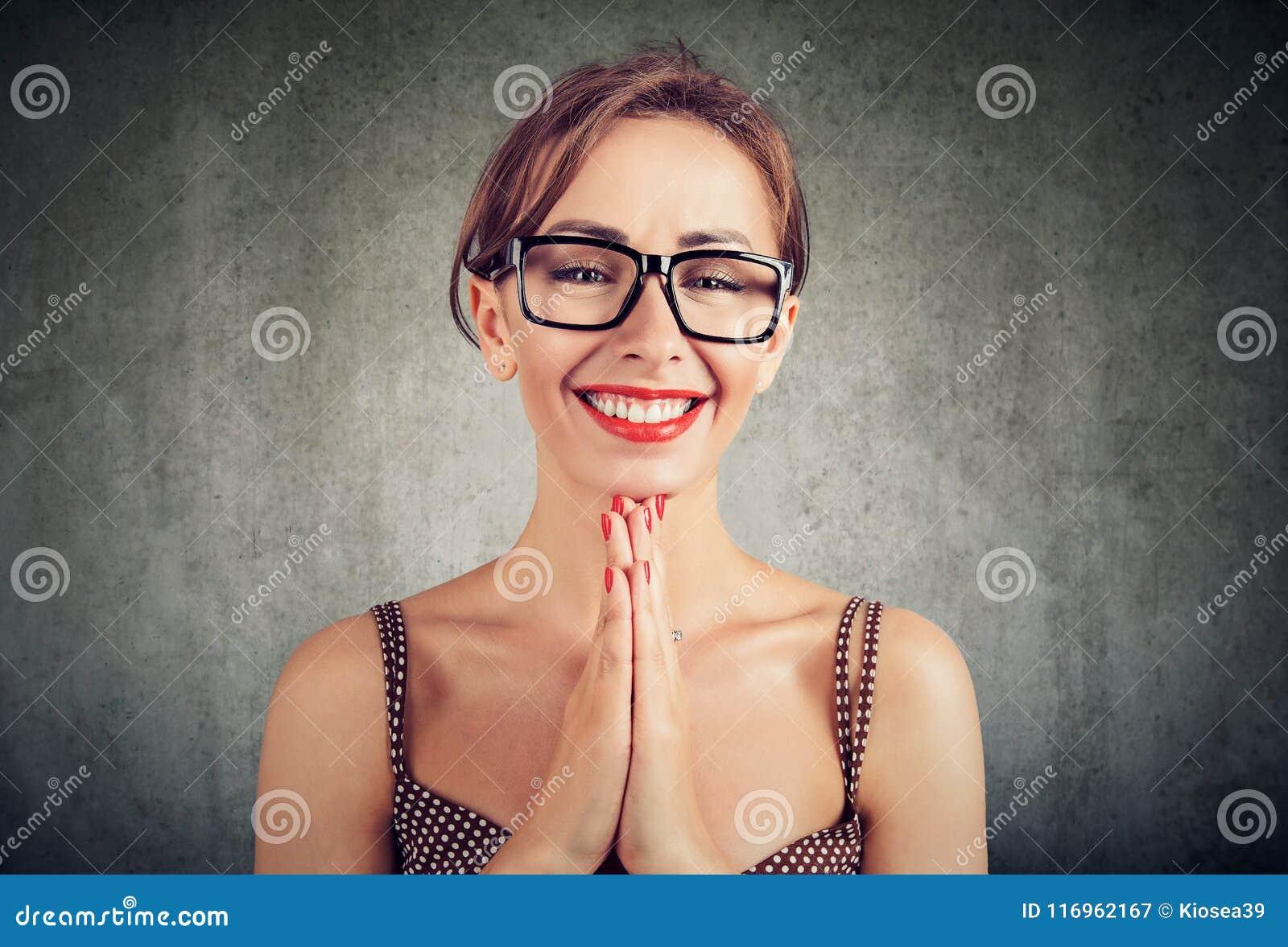 La jolie femme avec des paumes ensemble, a une expression heureuse de visage, demandant à quelqu un une faveur