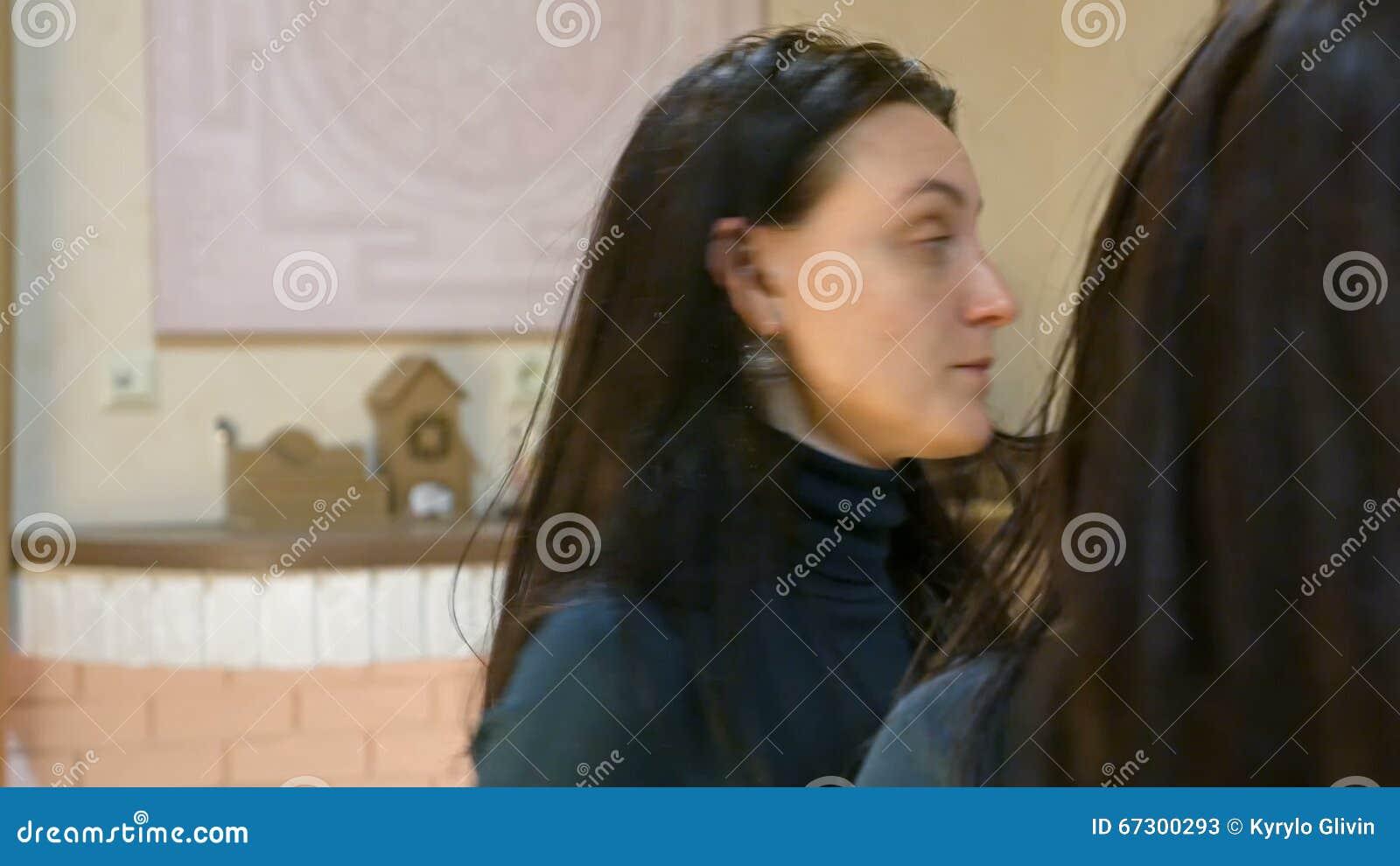 La jolie femme de brune applique le maquillage sur ses yeux clips