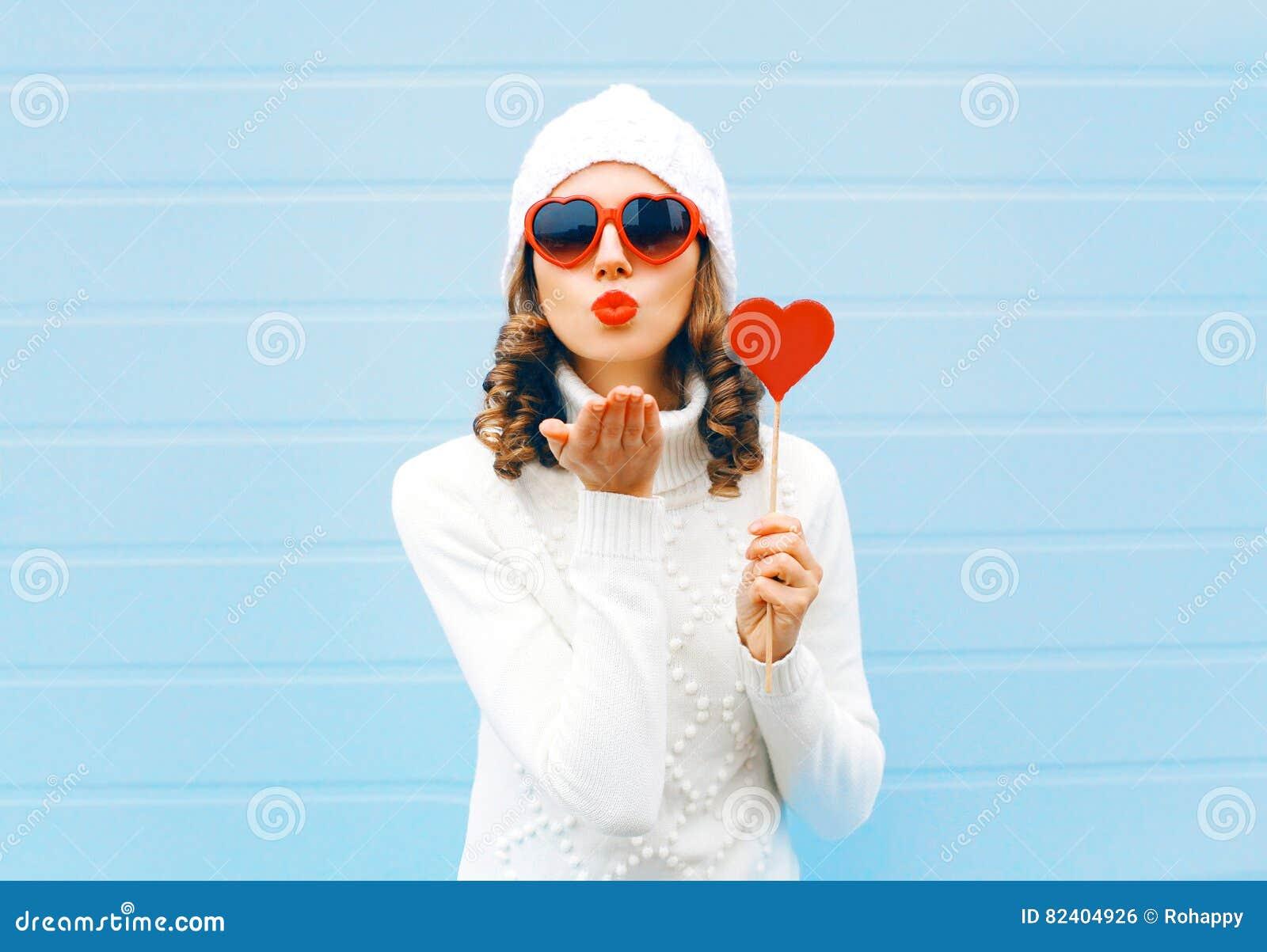 La jolie femme de portrait soufflant les lèvres rouges envoie à coeur de lucette de prises de baiser d air les lunettes de soleil