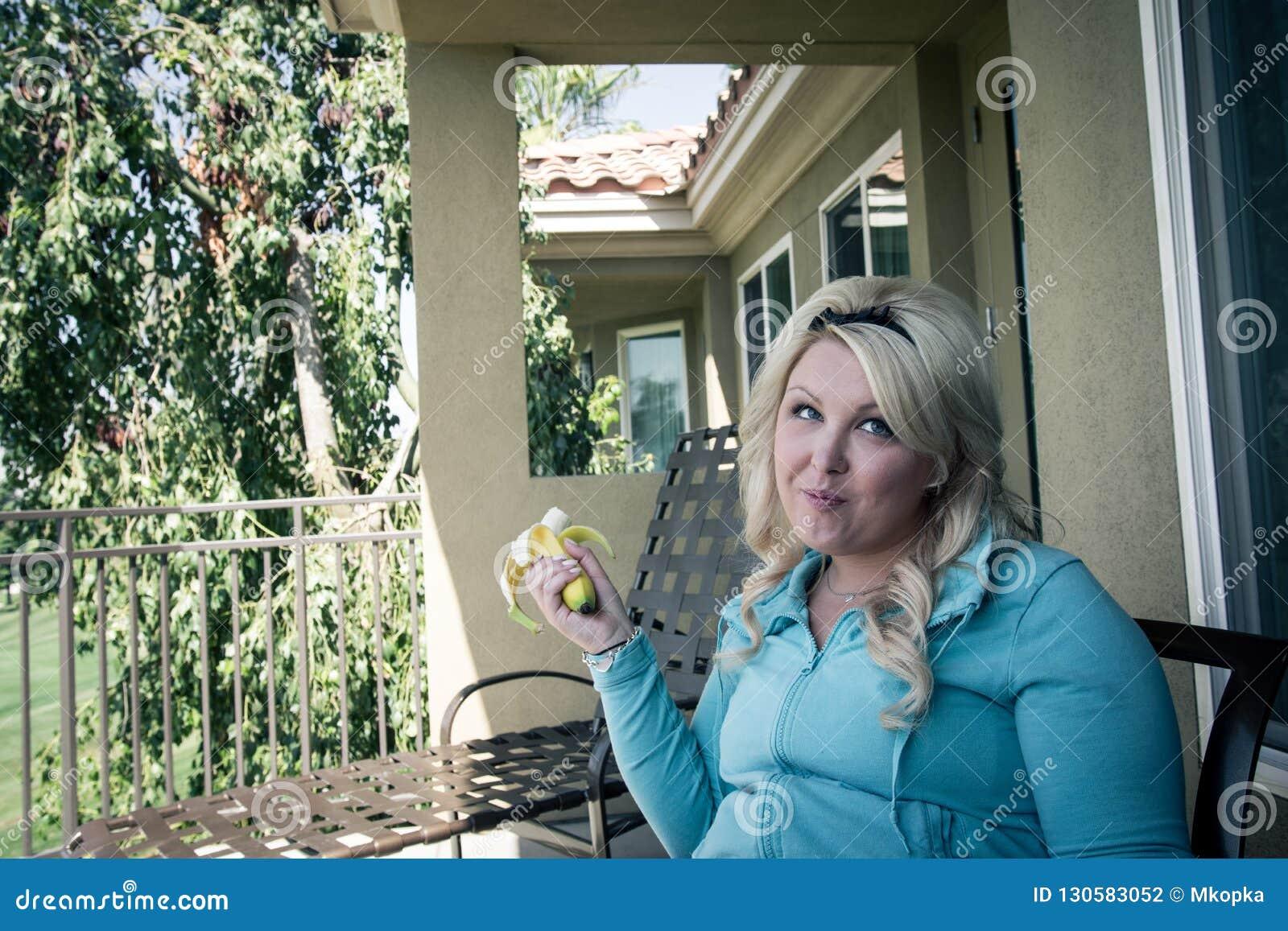 La jolie femme féminine blonde mange une banane sur un patio extérieur