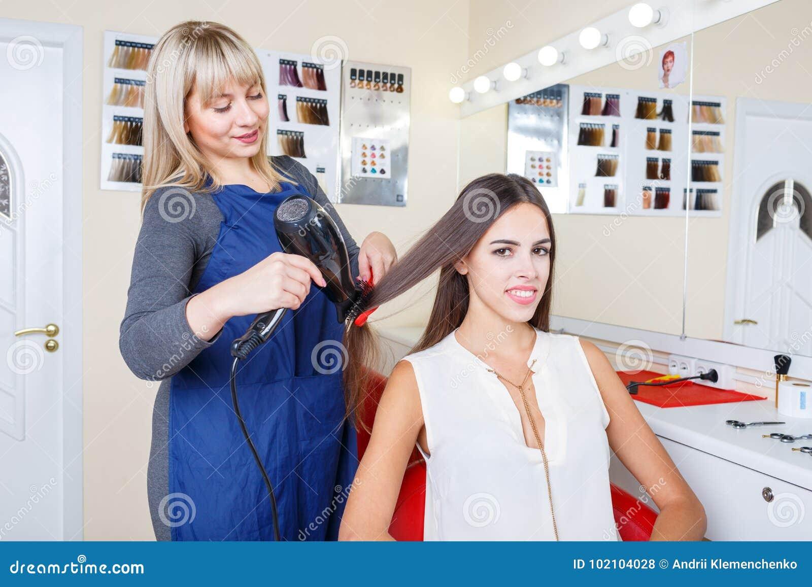La jolie femme positive dans un raseur-coiffeur lui obtenant des cheveux a teint sur un fond brouillé Concept de Hairstyling