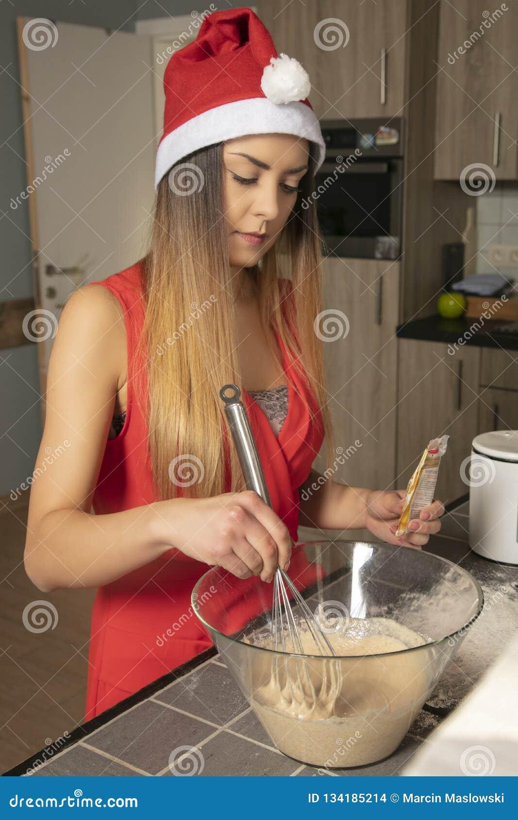 La jolie fille dans l habillement de Noël prépare le gâteau pour faire, elle ajoute des ingrédients