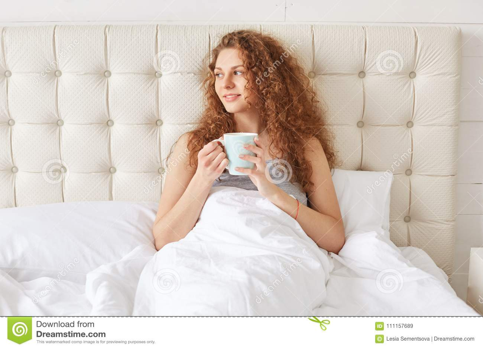 La jolie jeune femme avec les cheveux bouclés prend le café aromatique i de matin