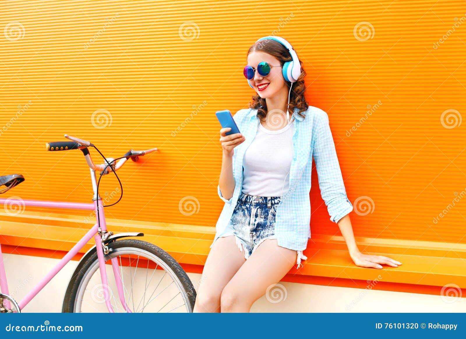La jolie jeune femme de mode écoute la musique utilisant le smartphone près de la rétro bicyclette urbaine au-dessus de l orange