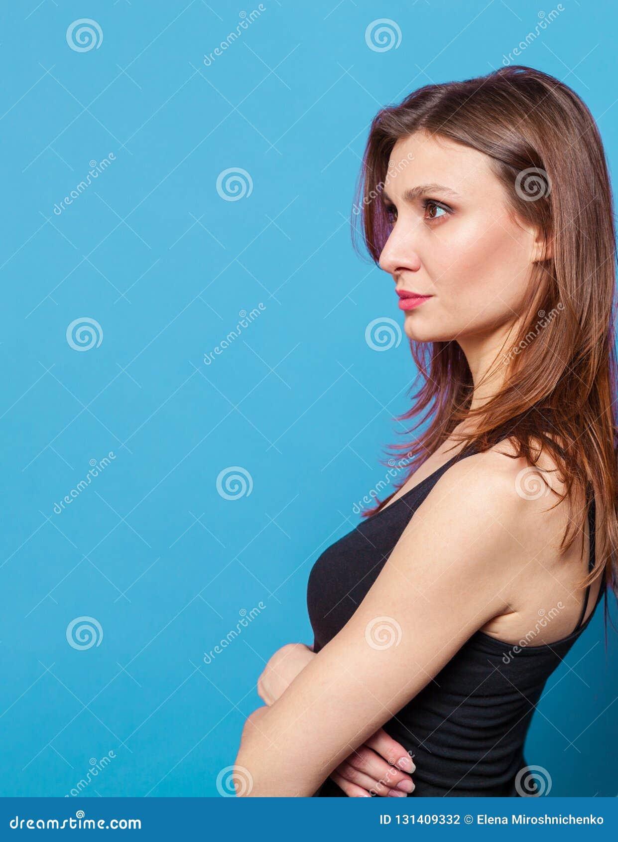 La jolie jeune femme restant de nouveau au mur avec des mains a croisé