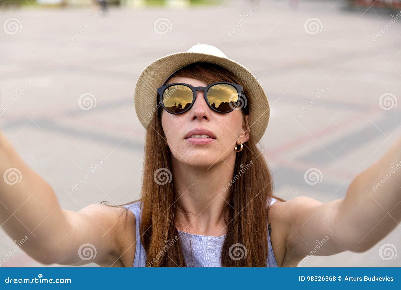 La jolie touriste de jeune femme prend le portrait de selfie sur la place de ville, Riga, Lettonie La belle étudiante prend la ph