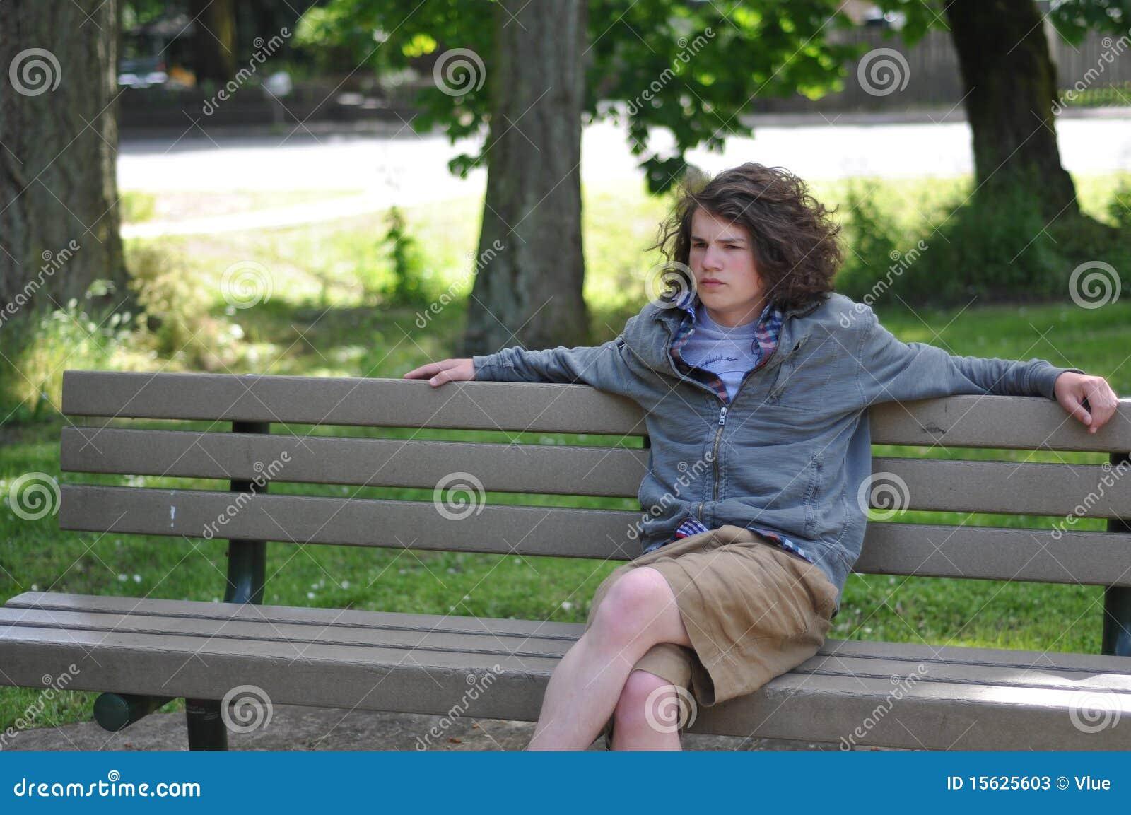 La juventud sin hogar se sienta en banco