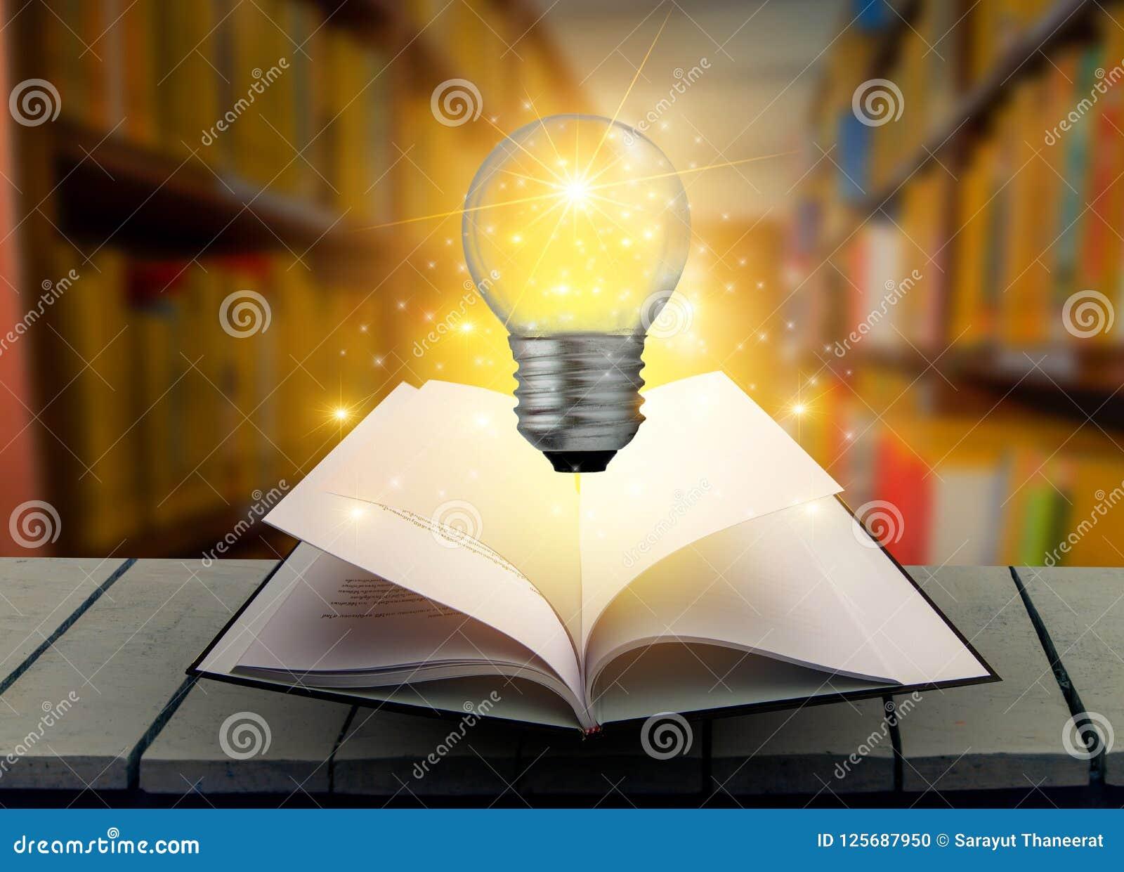 La lampadina del libro è sulla tavola Legno in libro delle biblioteche e libro stracciato della lampadina vecchio su una lettura