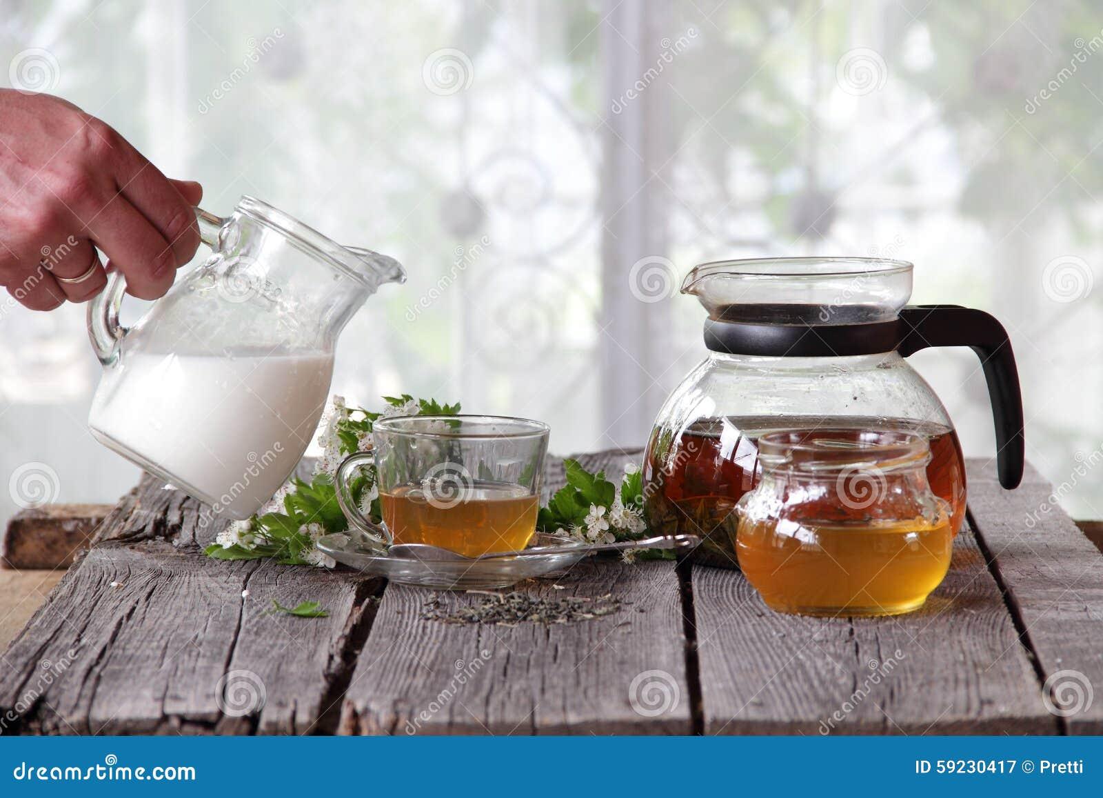 La leche vierte una taza transparente con té