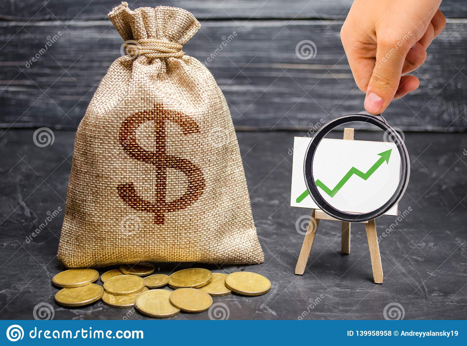 La lente d ingrandimento sta esaminando la freccia verde su sul grafico e su una borsa con soldi concetto dei profitti aumentanti