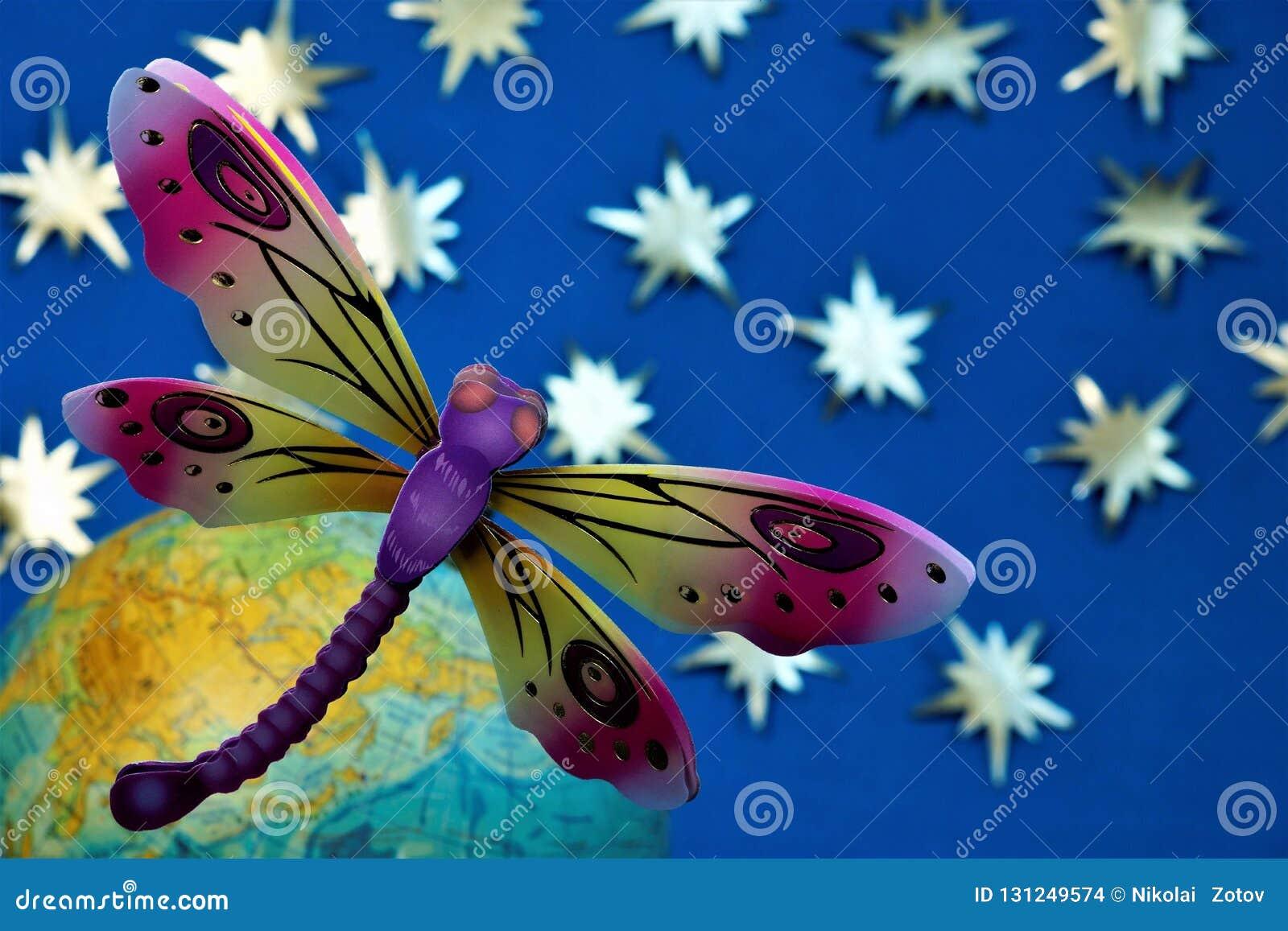 ed5e08f9bd El colorante brillante del día de fiesta de la libélula asoma sobre la  tierra contra el cielo estrellado borroso