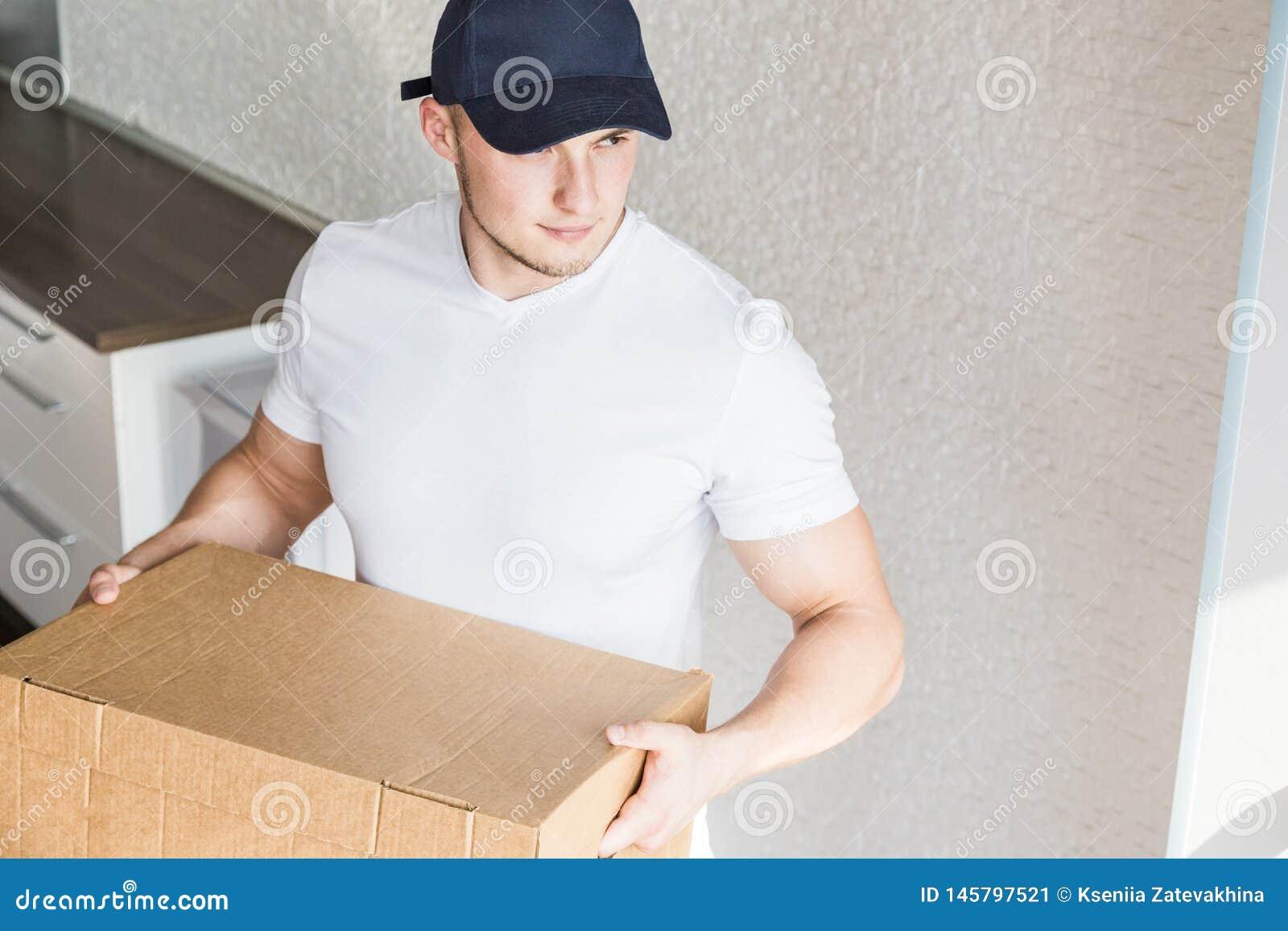 La livraison forte, bo?tes en carton musculaires de chargement d homme pour se d?placer ? un appartement travailleur professionne