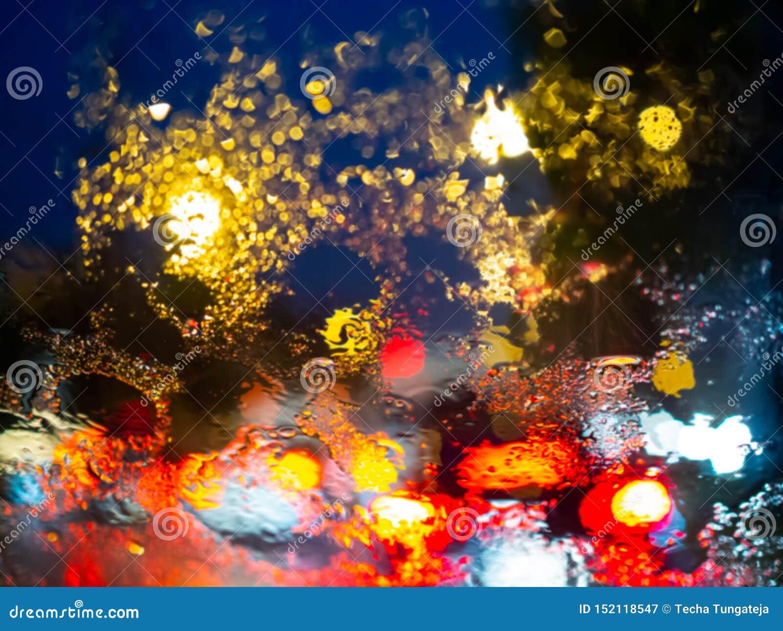 La lluvia borrosa cae en la ventanilla del coche con el bokeh de la luz del camino en fondo del extracto de la estación de lluvia