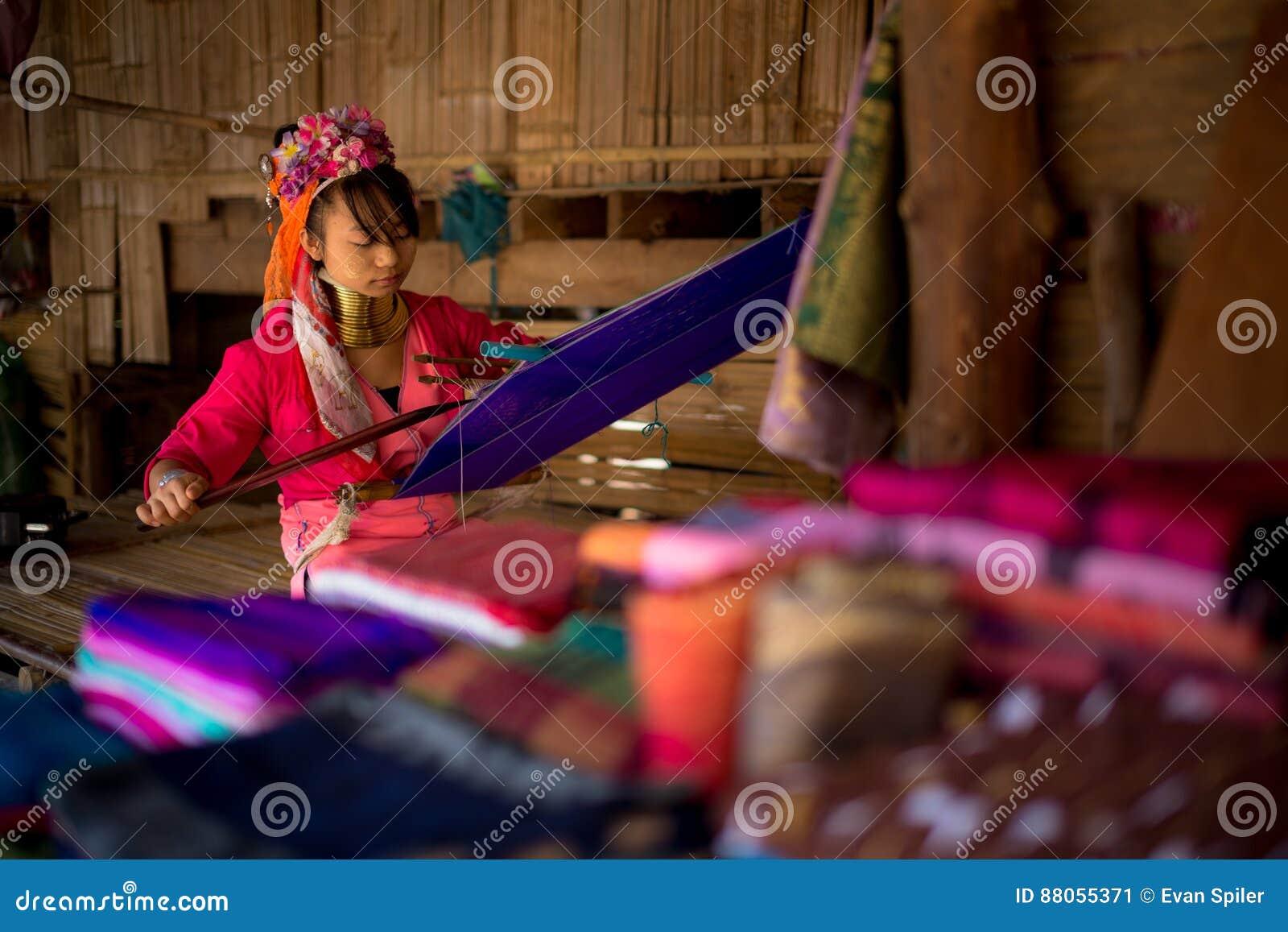 La longue femme étranglée de tribu de Karen tisse sur un métier à tisser en collines près de Chiang Mai, Thaïlande
