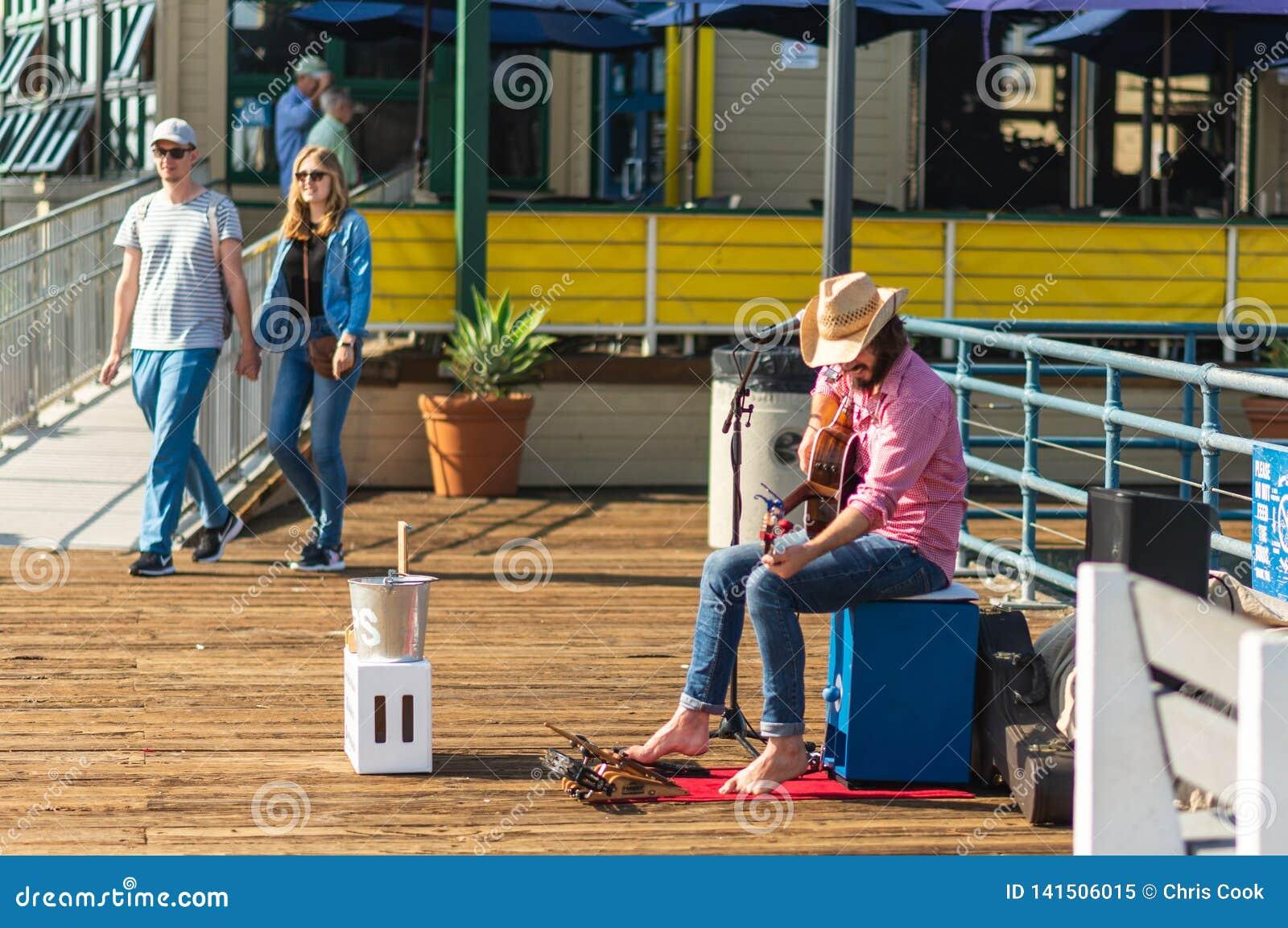 LA, LOS E.E.U.U. - 30 DE OCTUBRE DE 2018: Un busker canta para el dinero en Santa Monica Pier