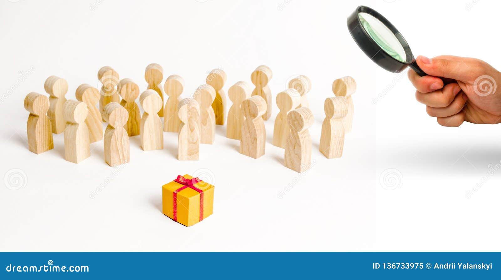 La loupe regarde le grand groupe de personnes regardant un cadeau Le concept de choisir un bon cadeau, un nombre limité