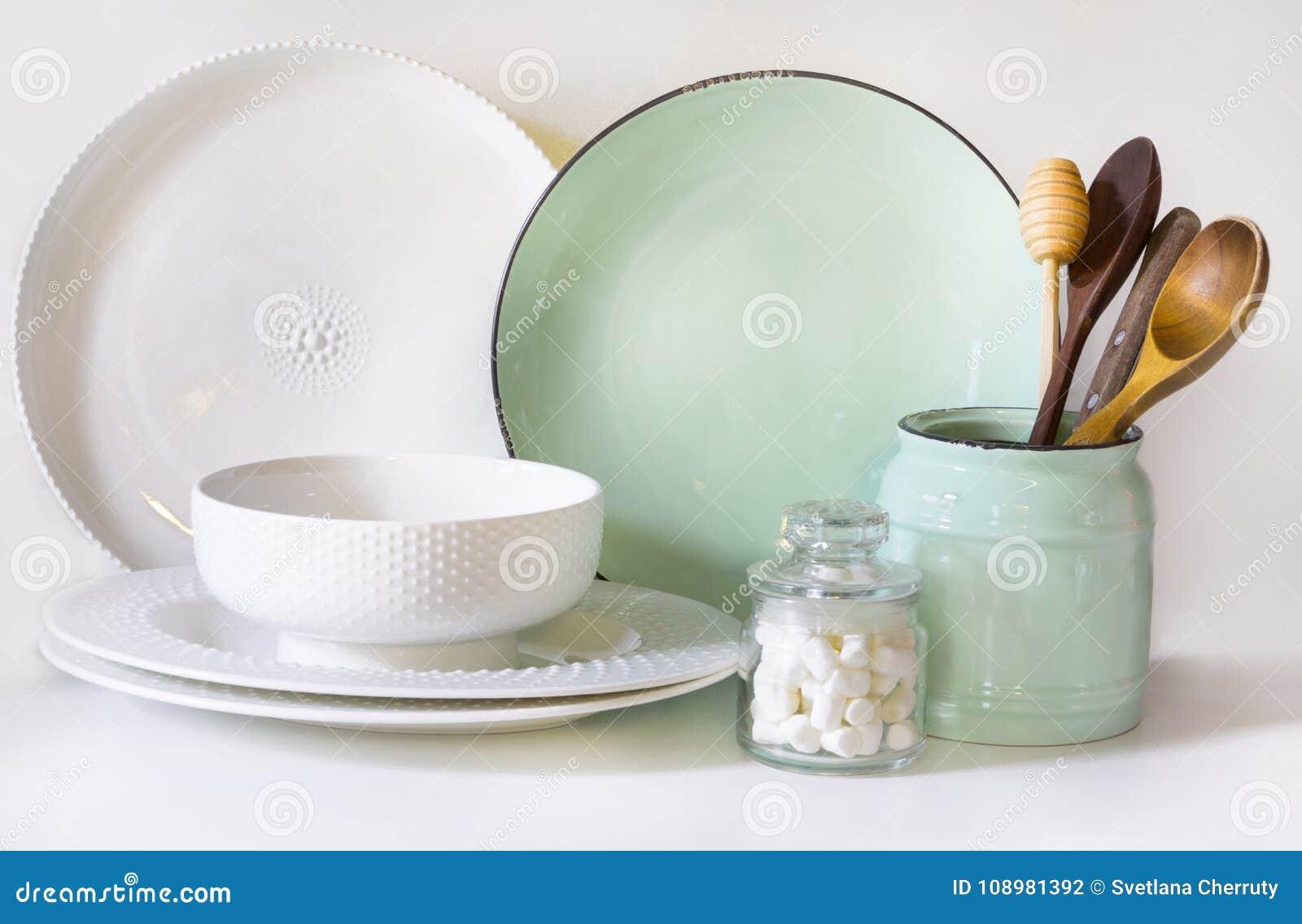 La loza, el vajilla, los utensilios y el otro diversos blanco y materia de la turquesa en tablero blanco Todavía de la cocina vid