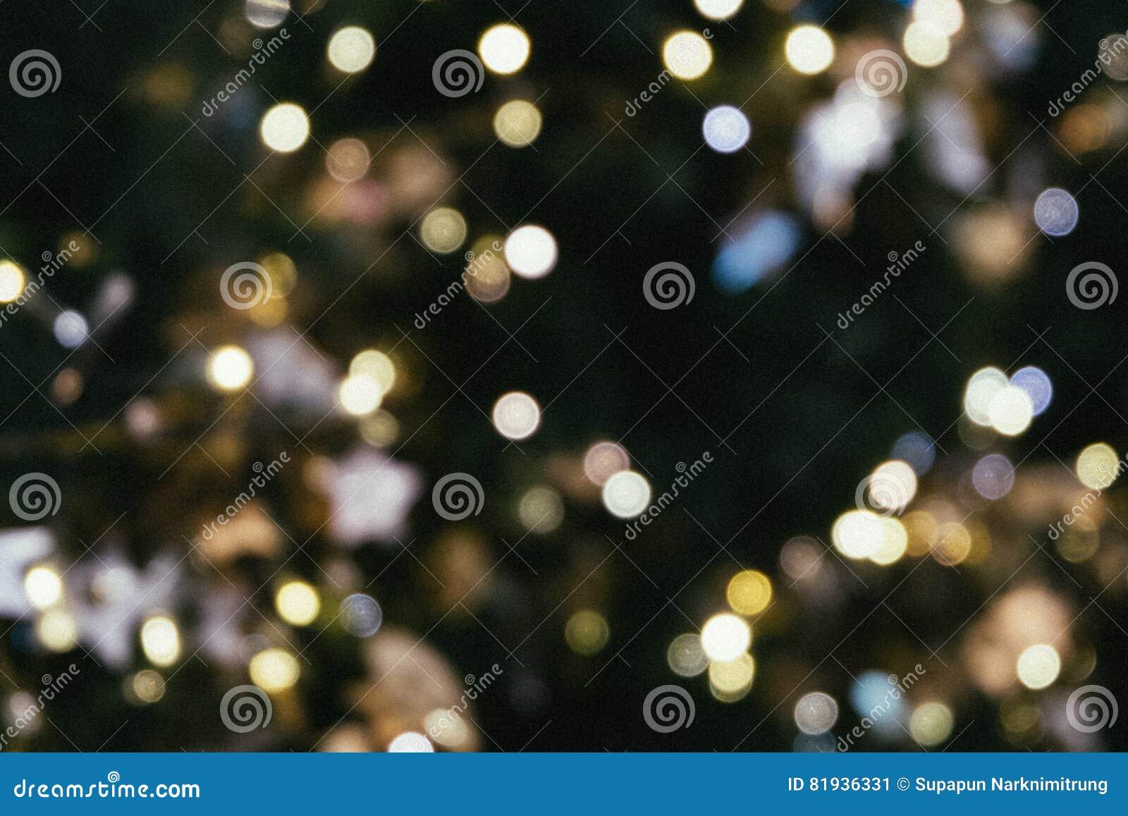 La luce del bokeh dell albero di Natale nel colore dorato giallo verde, fondo astratto di festa, offusca defocused con colore dei