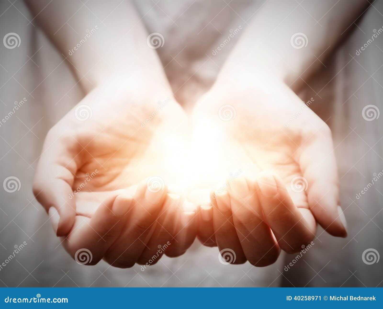 La luce in mani della giovane donna. Divisione, dare, offrente, protezione