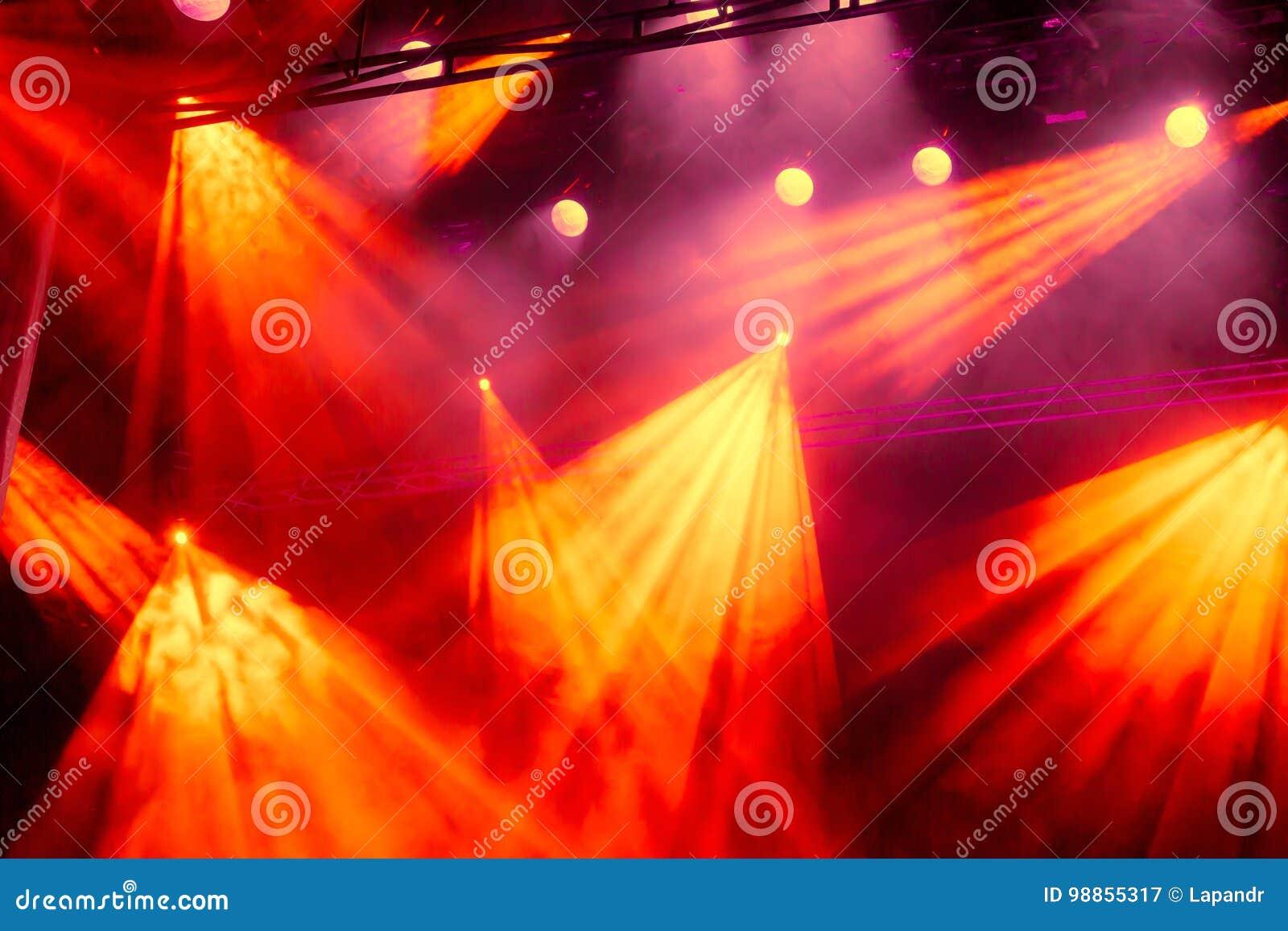 La lumière jaune et rouge rayonne du projecteur par la fumée au théâtre ou à la salle de concert Projecteur de hall de l éclairag