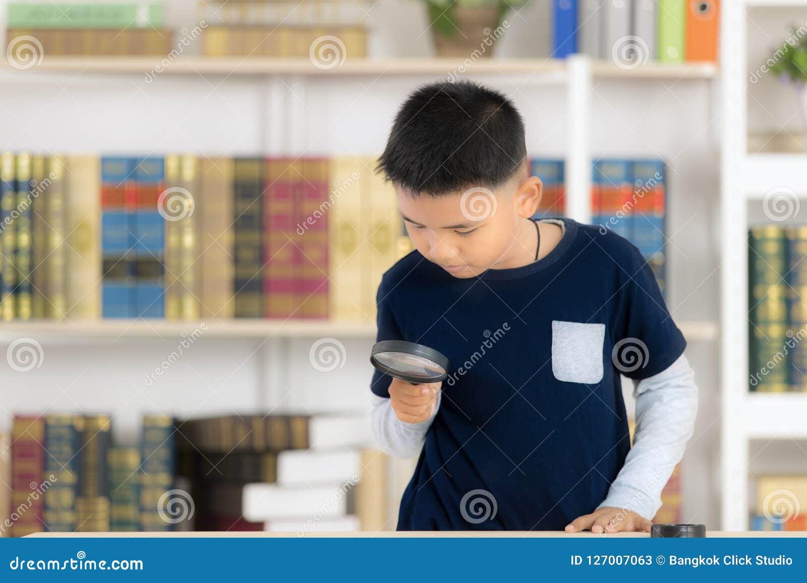 La lupa asiática joven de la sonrisa y del control del muchacho la biblioteca es
