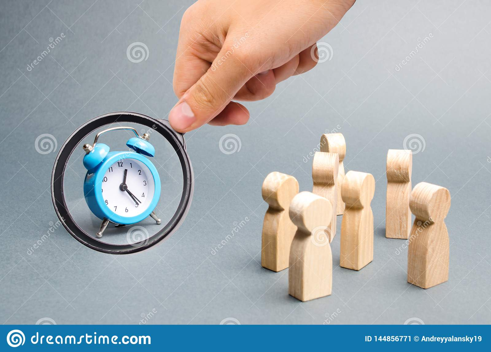 La lupa est? mirando el reloj azul Muchedumbre de miradas de la gente en el reloj Encadenan a la gente de la atenci?n al reloj