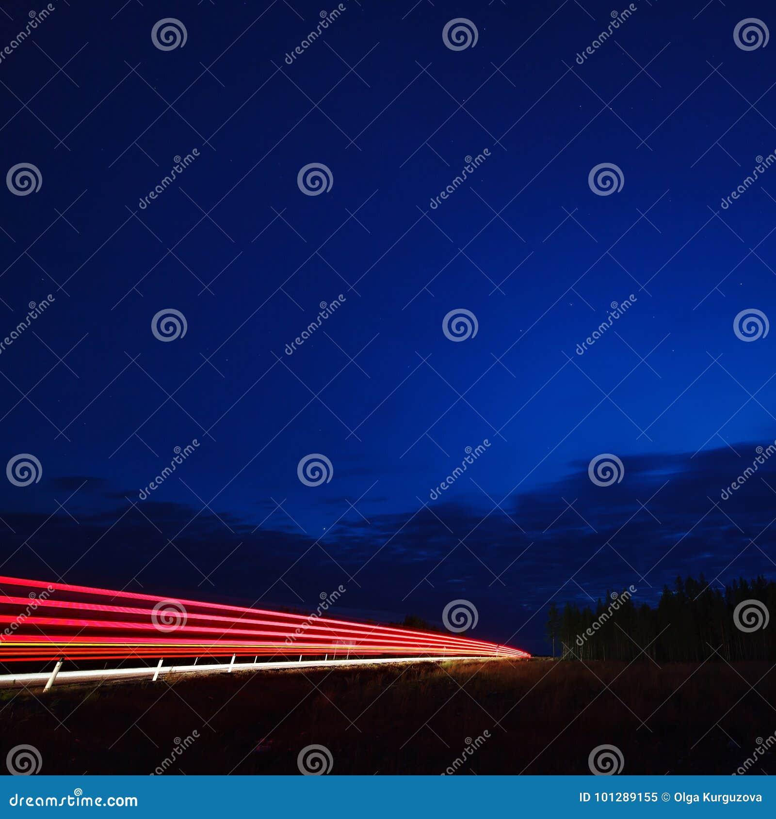La luz de los coches en la carretera en el cielo estrellado de la noche