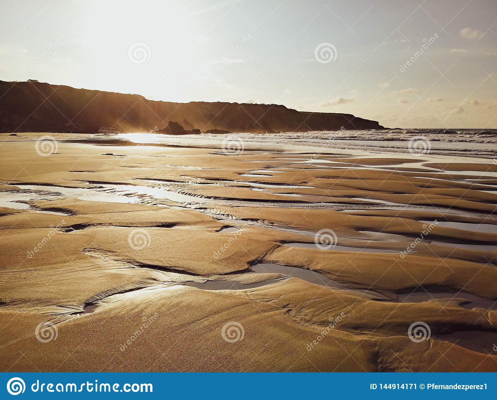 La luz de una puesta del sol m?gica reflejada en la arena de la playa