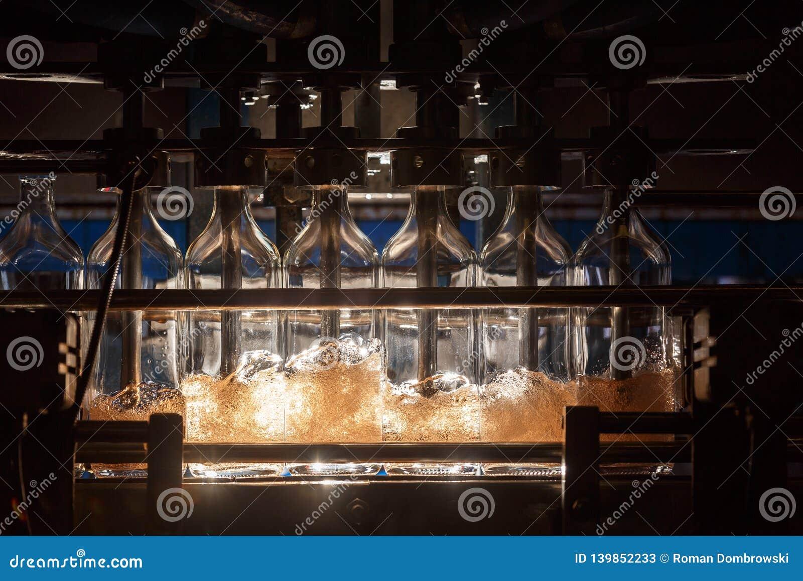 La máquina de rellenar automática vierte el líquido en las botellas de cristal Producción de la elaboración de la cerveza Fondo i