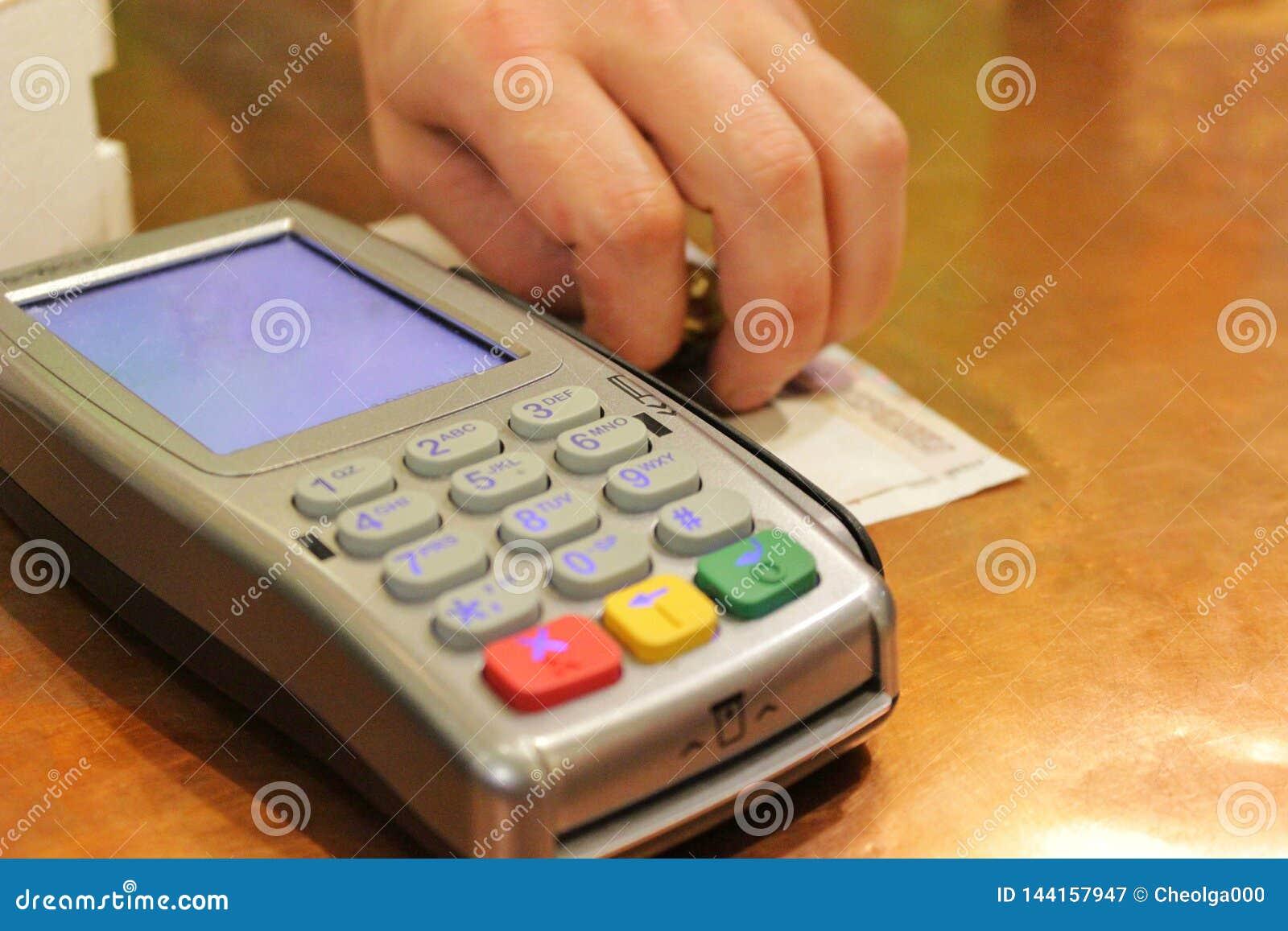 La máquina de la tarjeta de crédito y la mano de un hombre pone efectivo