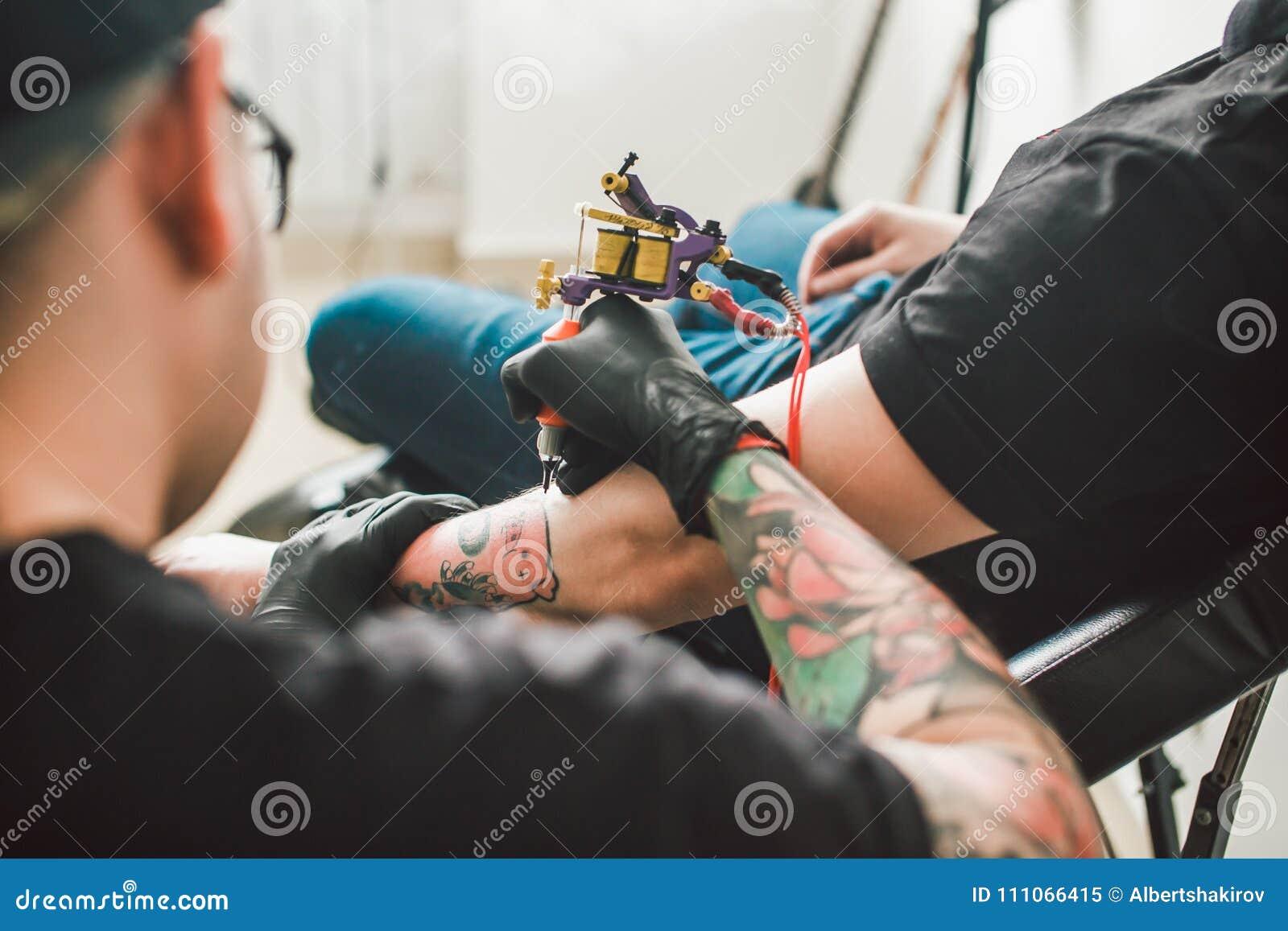 La máquina del tatuaje hace el dibujo en la mano masculina